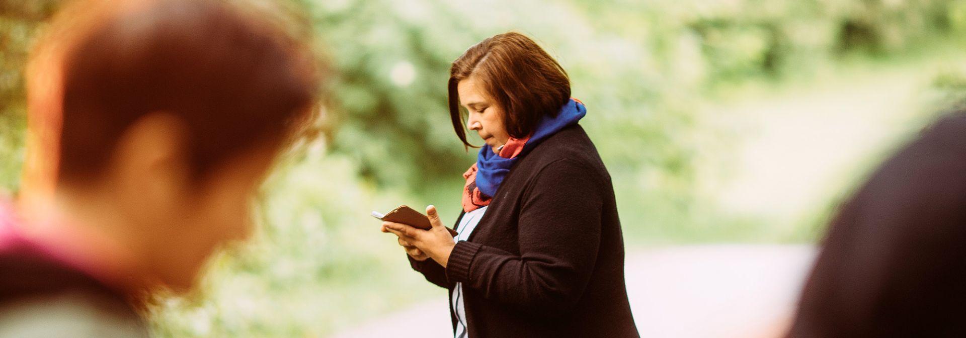 Nainen katsoo puhelinta, etualalalla näkyy epäselvästi ihminen.