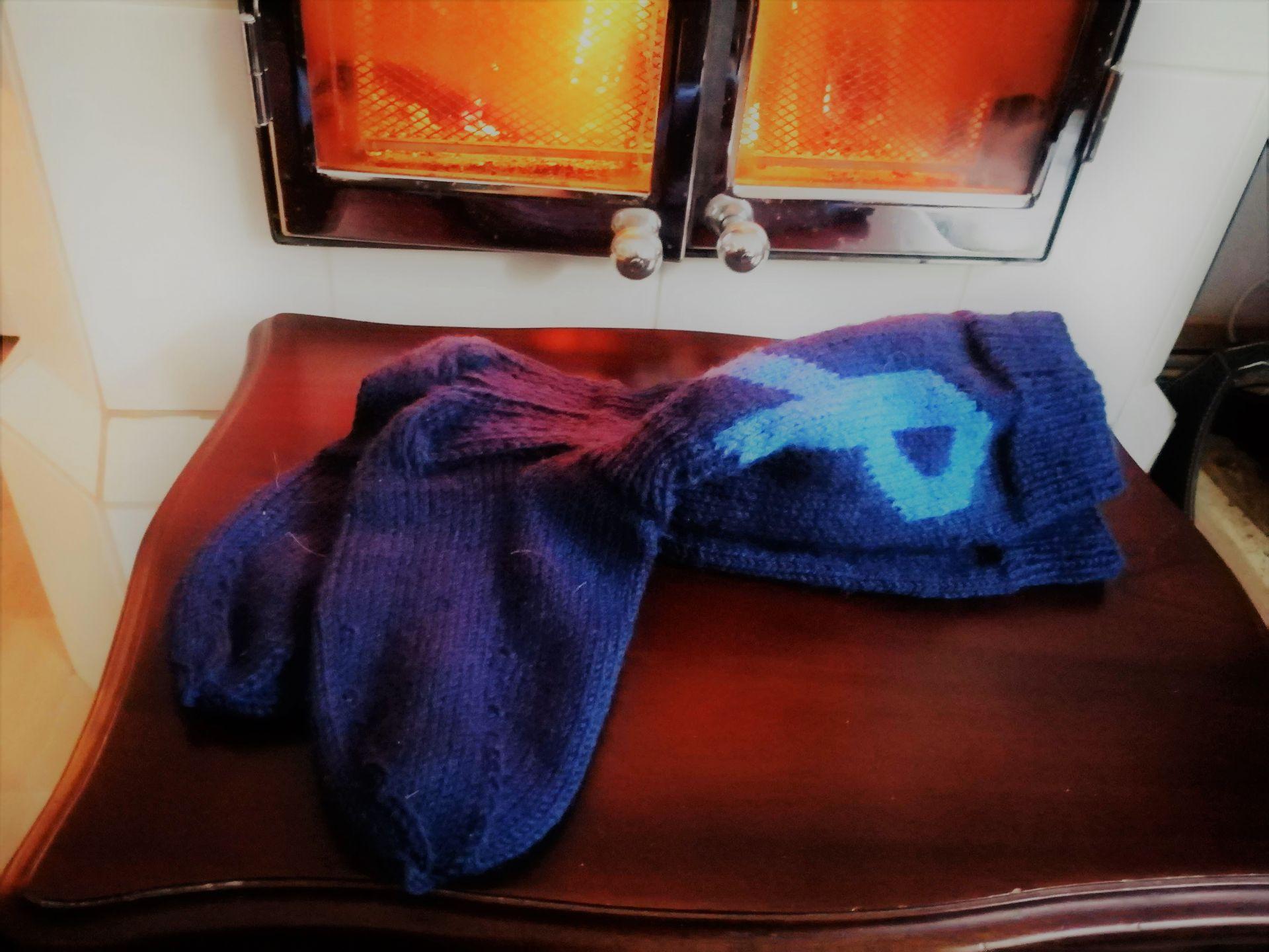 Kaksi villasukkaa penkin päällä takan edessä.