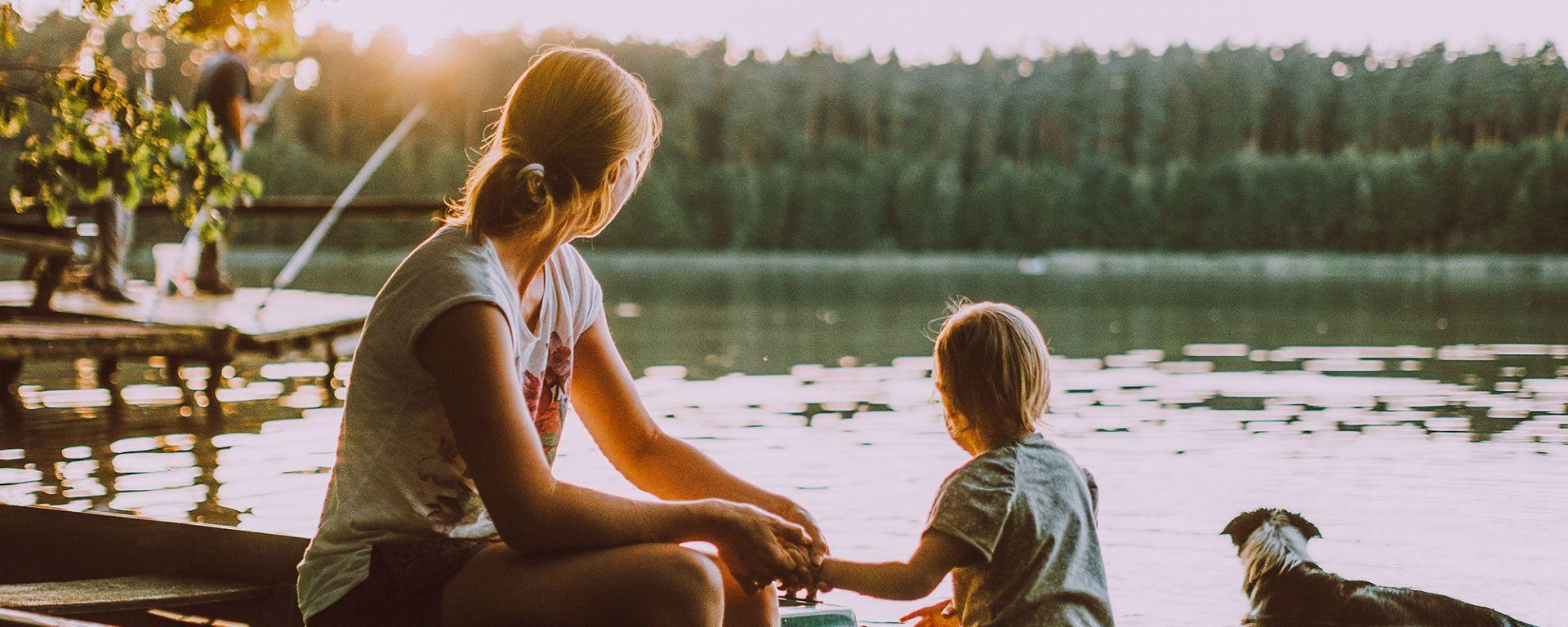 Nainen istuu rannassa soutuveneessä. Hän pitää kiinni pienen lapsen kädestä. Vieressä vedessä seisoo myös koira. Kaikki kolme ovat takaraivot kameraa kohden, he katsovat järvelle, missä aurinko on juuri laskemassa.