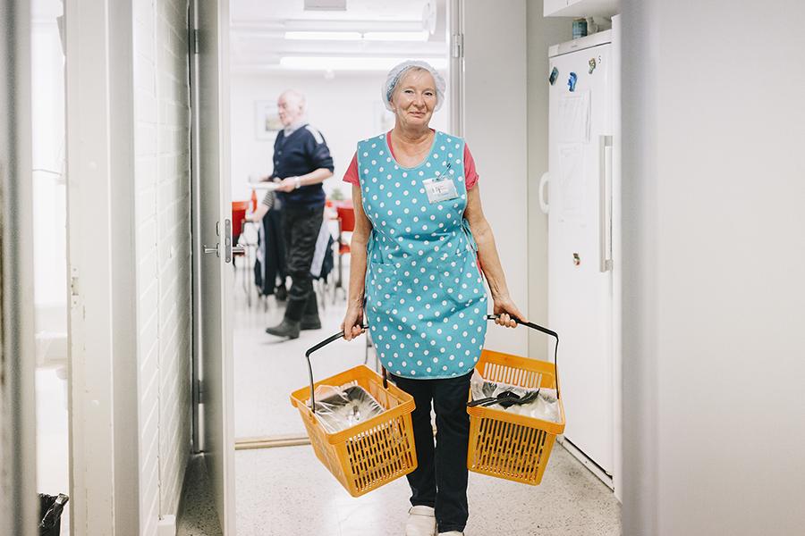 Nainen kantaa kahta ruokakoria