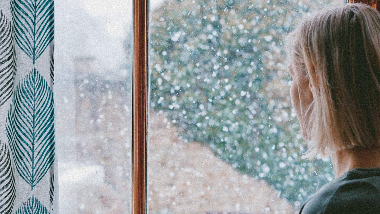 Nainen katsoo selin ulos ikkunasta, ulkona sataa lunta.