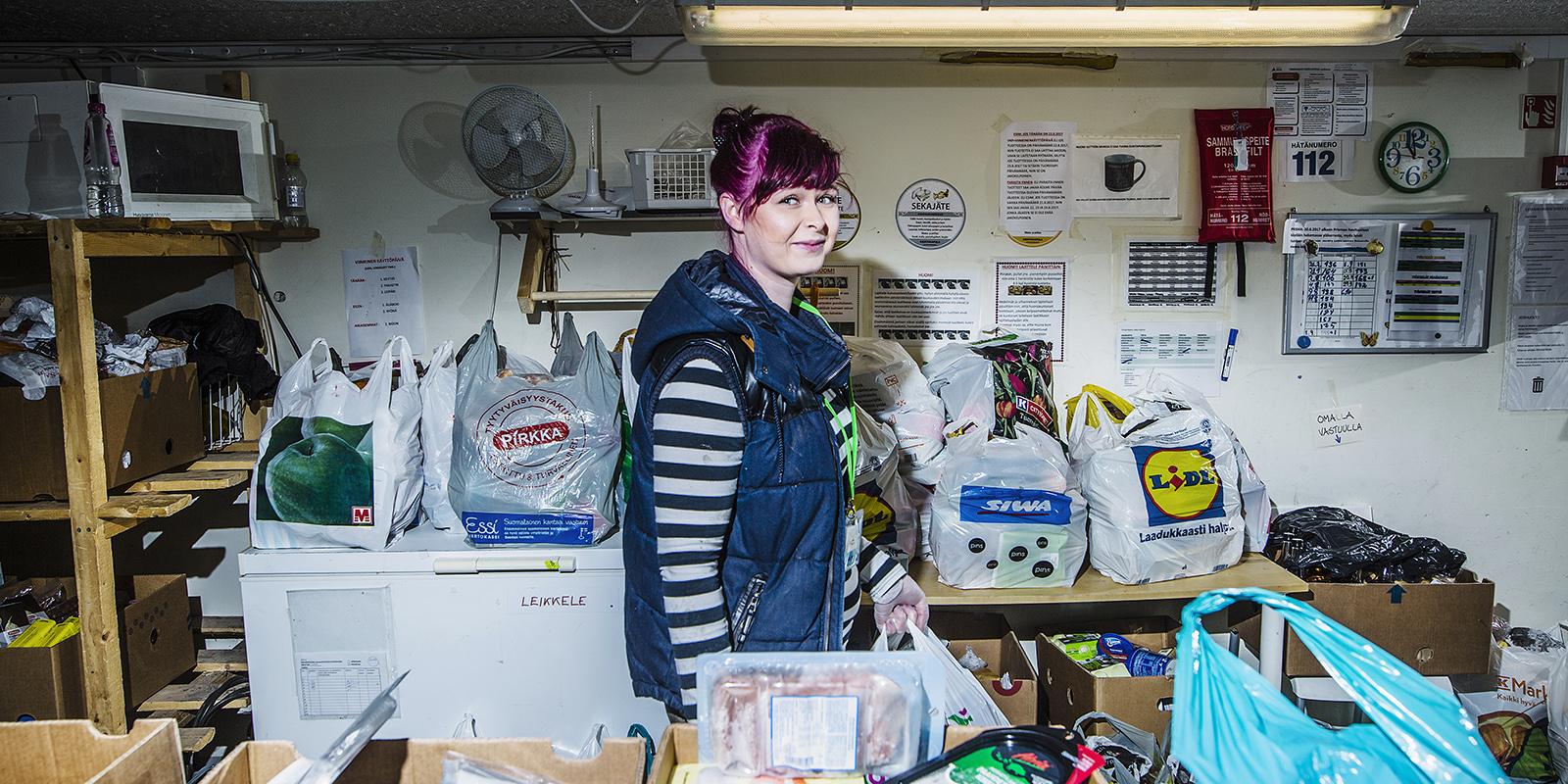 Nainen ruoka-apukassien keskellä