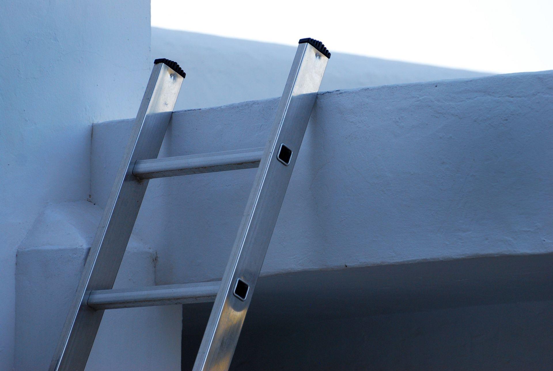 Alumiinitikkaiden yläpää nojaa seinään, jonka yläpuolella on ikkuna.