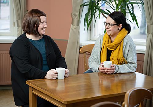 Kaksi naista kahvikuppien kanssa pöydän äärellä