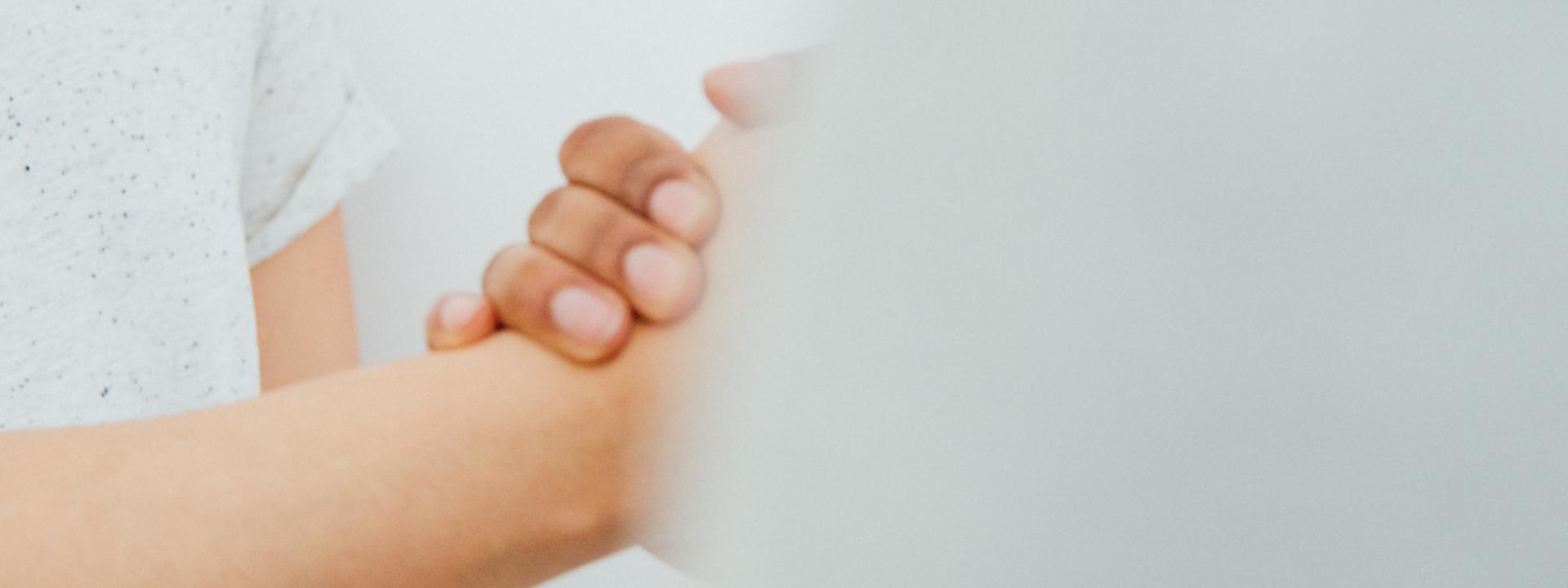 Kaksi kättä pitelemässä toisiaan. Valkoisia paitoja.