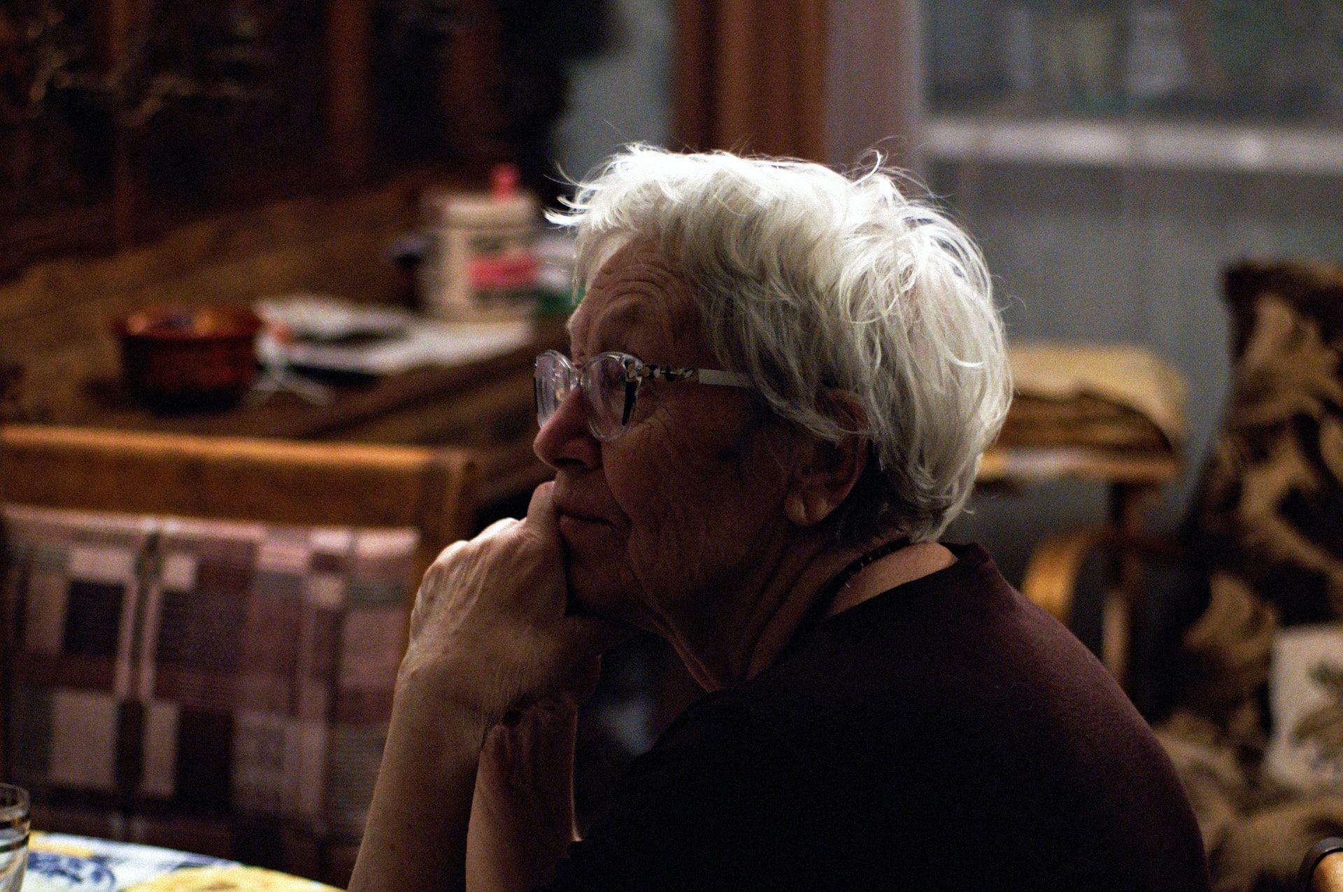iäkäs nainen istuu pöydän ääressä