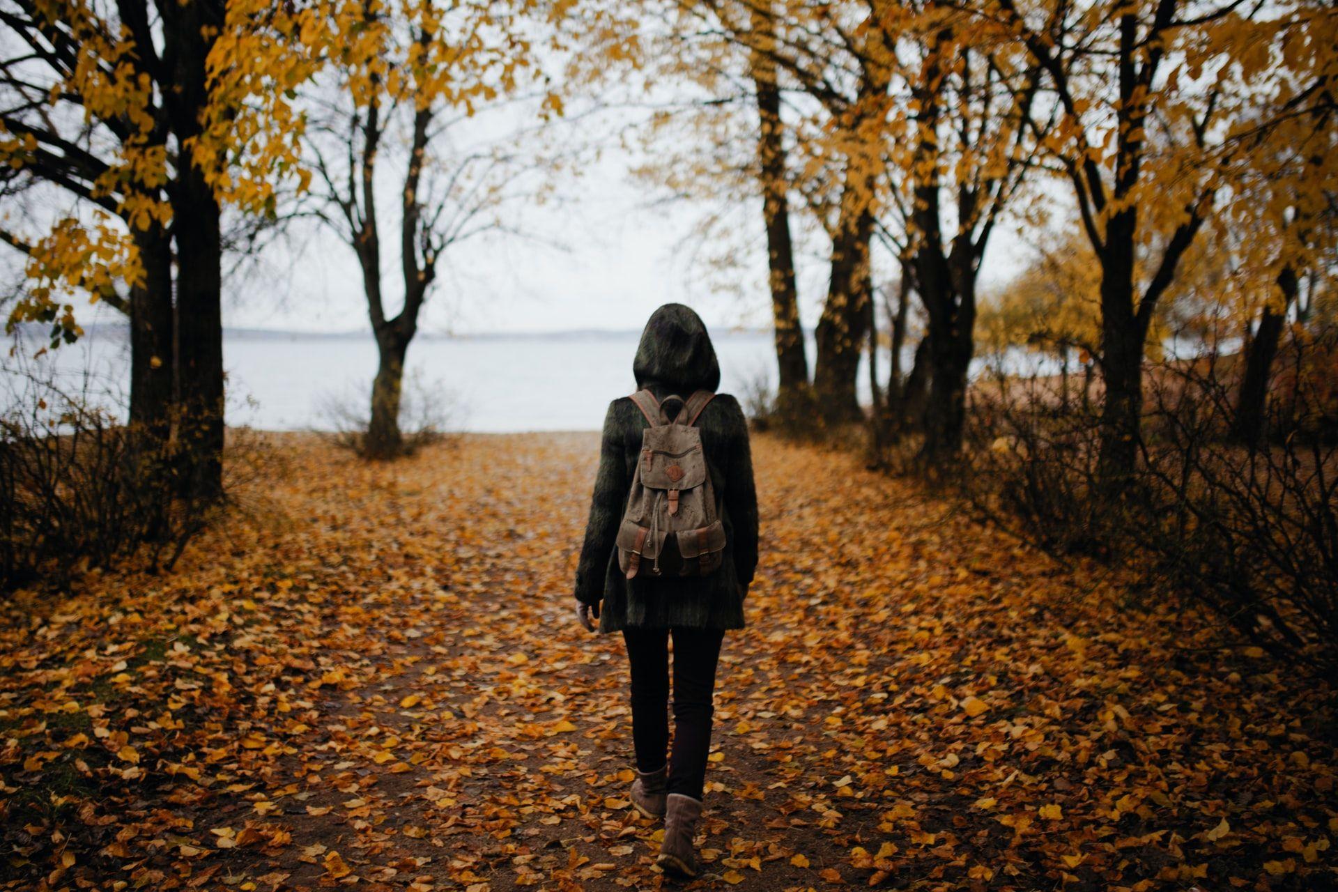 Nainen kävelee syksyisellä tiellä