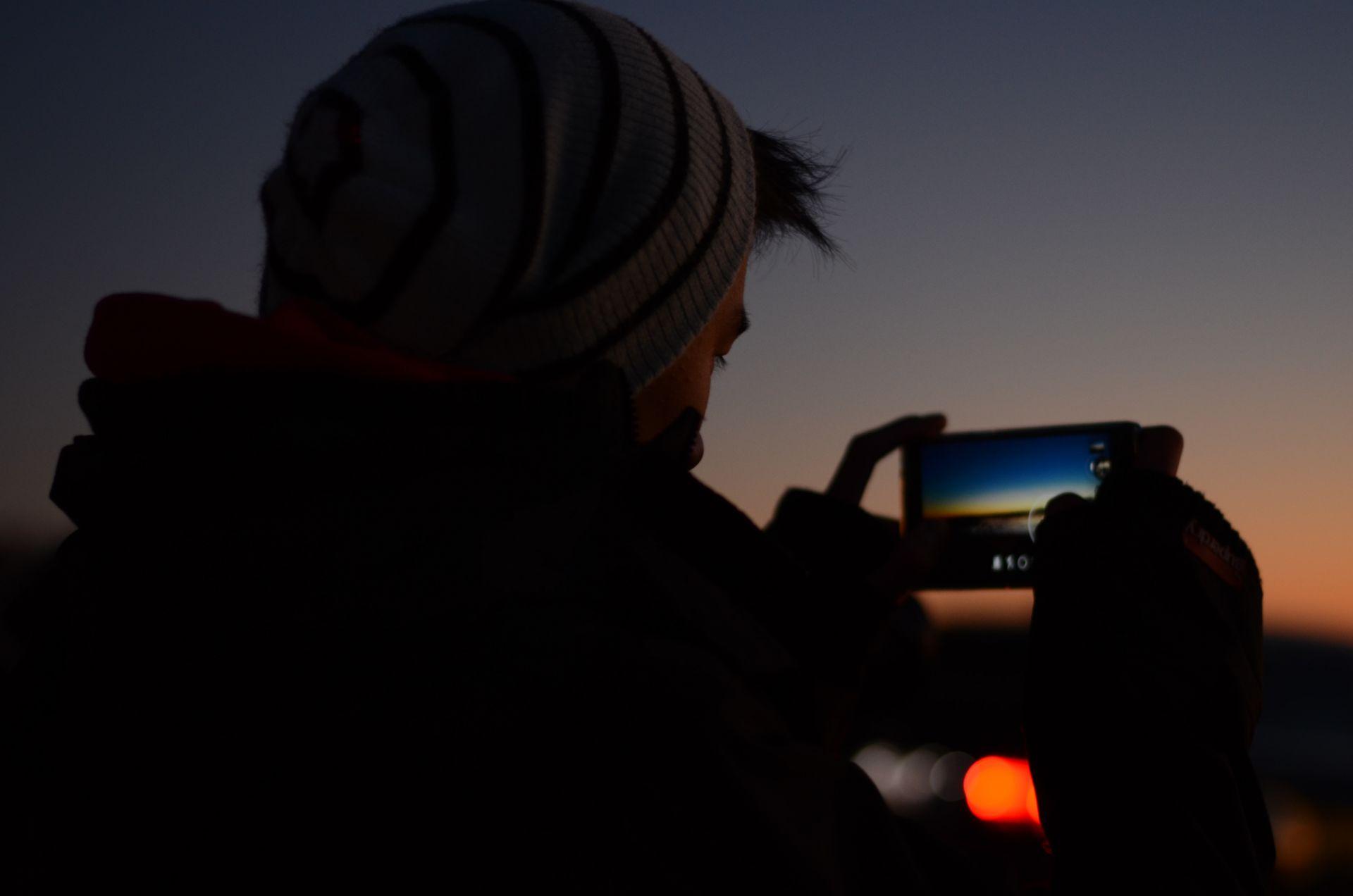 Pipopäinen henkilö ottaa älypuhelimella maisemakuvaa pimenevässä illassa.