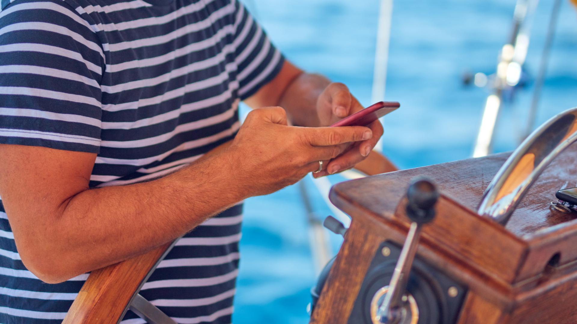 henkilö ohjaa purjevenettä ja räplää älypuhelinta samalla