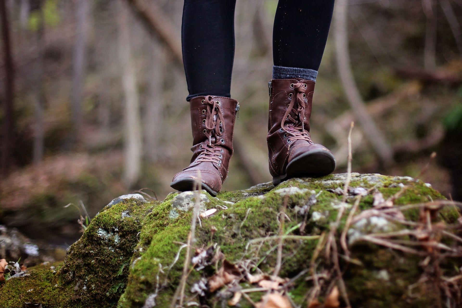 Kengät sammaleisella kivellä metsässä.