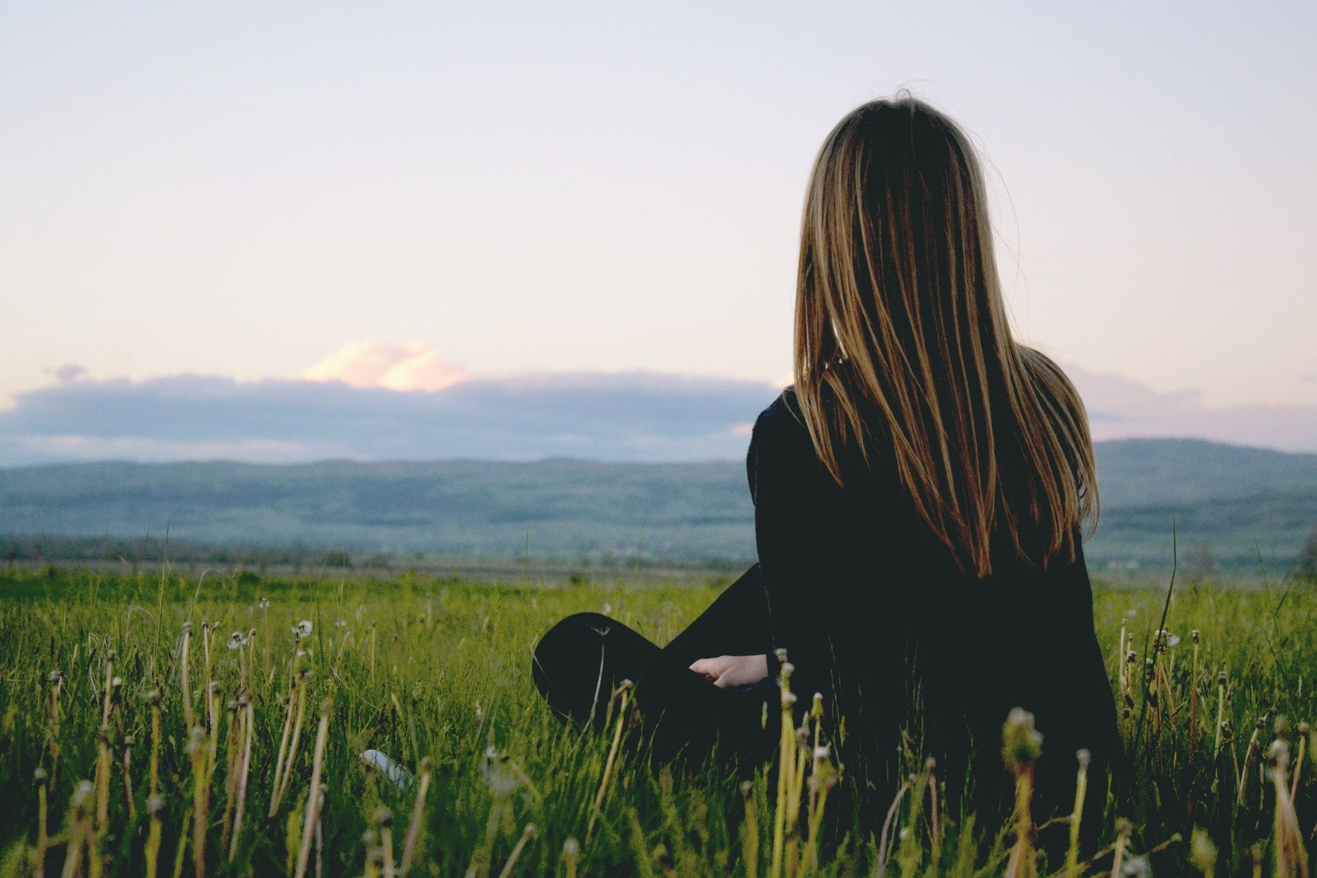 Nainen istuu ruohikossa