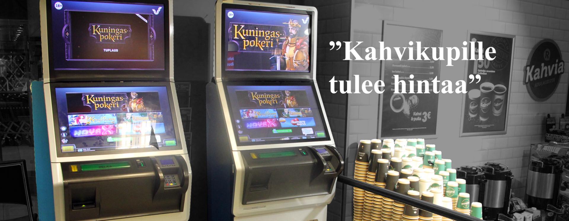 Kioskilla olevat kaksi peliautomaattia, joissa näytöllä lukee isolla Kuningaspokeri. Vieressä pino pahvisia kahvikuppeja ja isoja termareita.