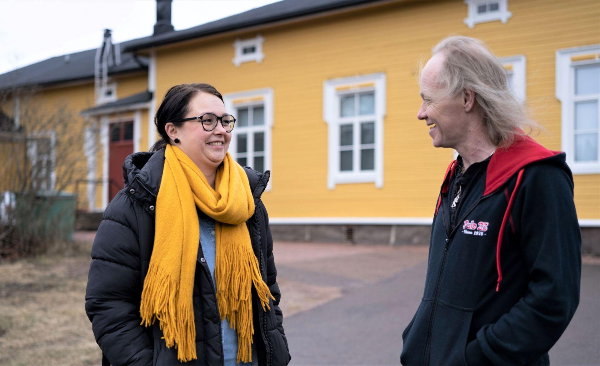 Kaakkois-Suomen Sininauhan ohjaaja ja asukas keltaisen talon edessä.