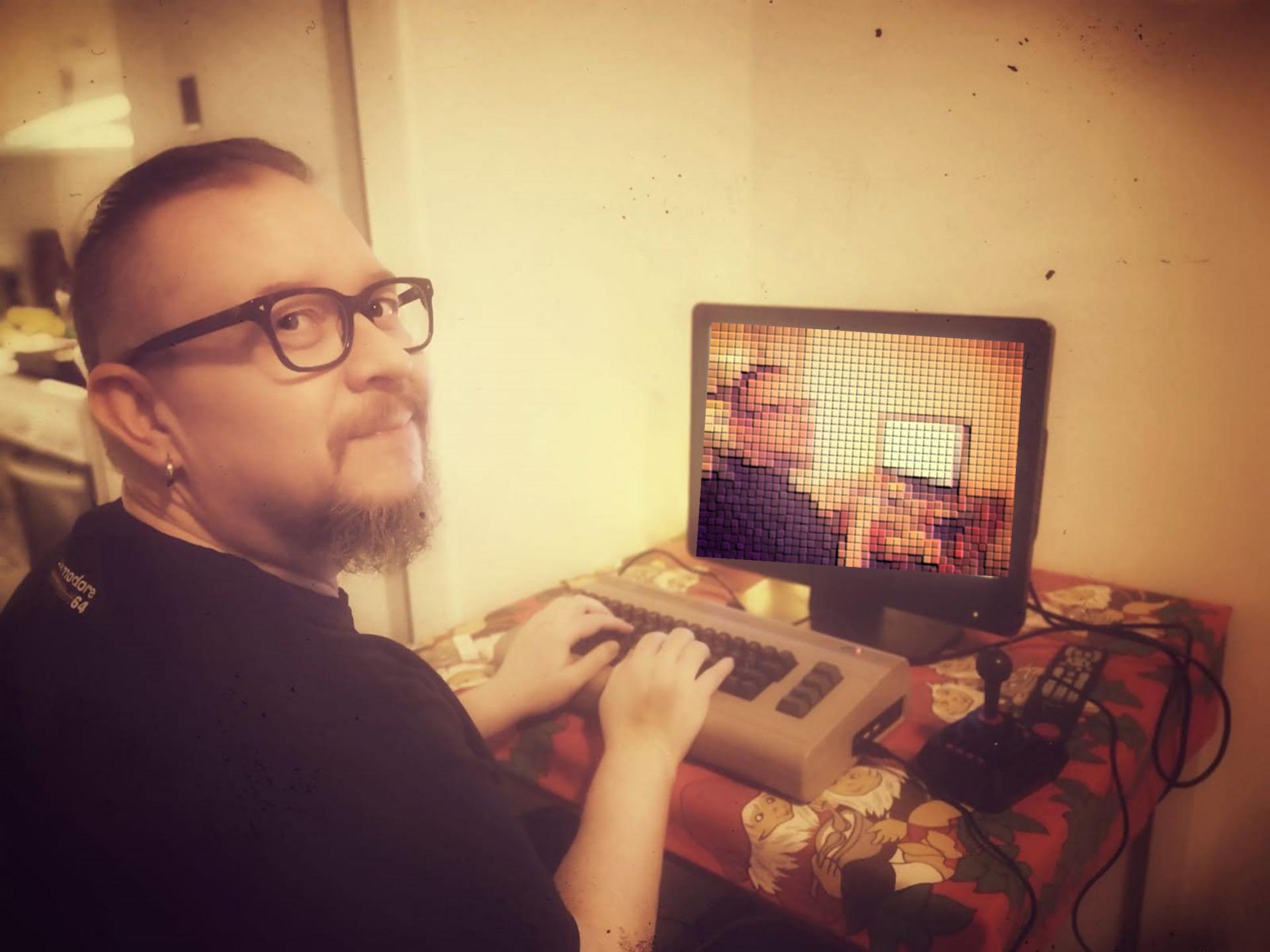 Hymyilevä silmälasipäinen parrakas mies istuu tietokoneen ääressä sormet näppäimistöllä.