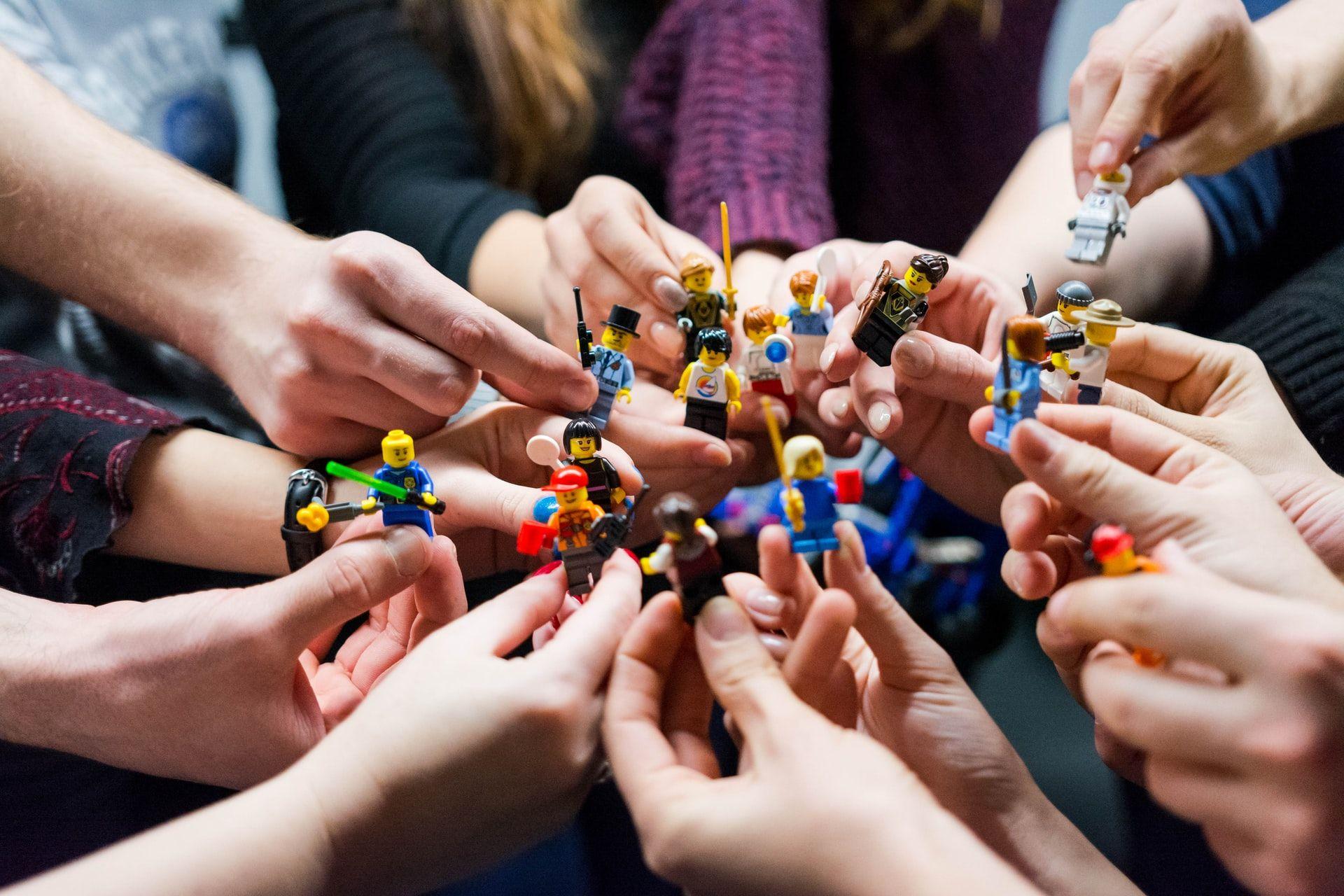 ryhmä ihmisiä pitelee ringissä lego-hahmoja