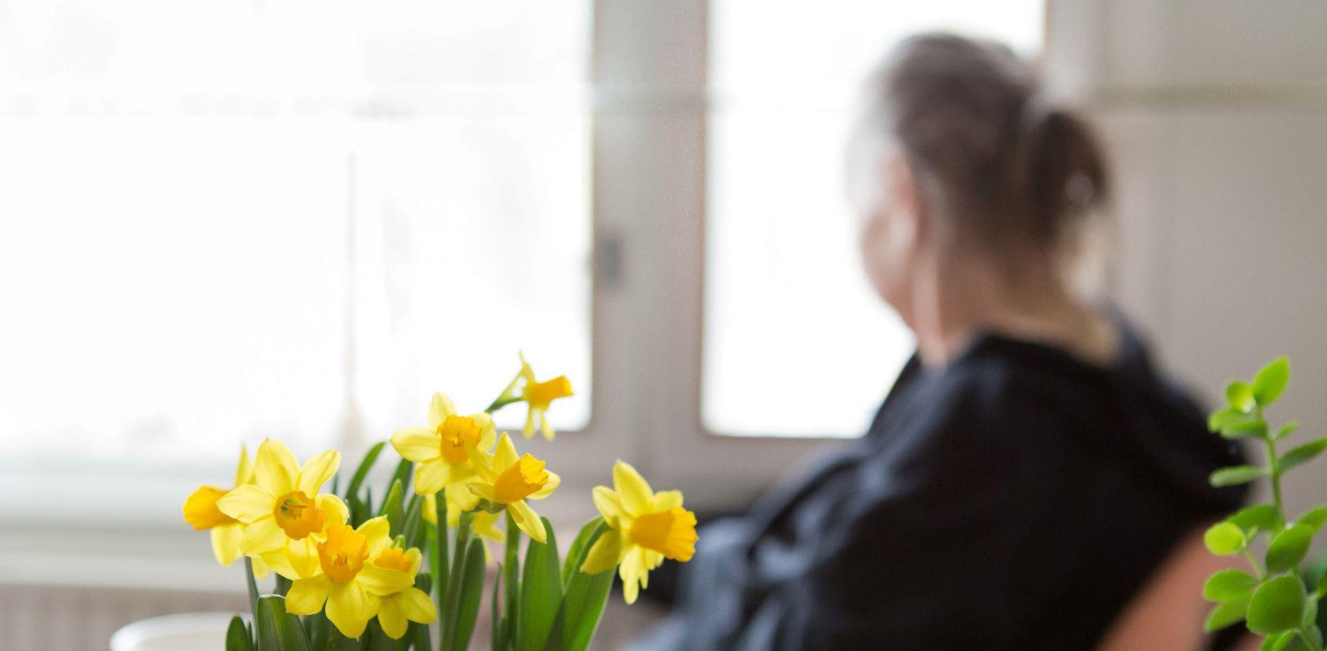 Nainen istuu ikkunan äärellä ja katsoo ulos.
