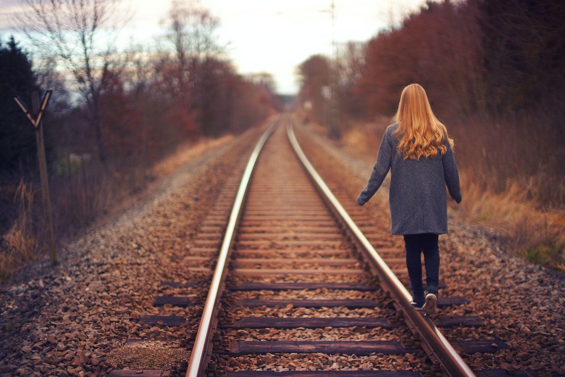 Nainen kävelee junaradalla