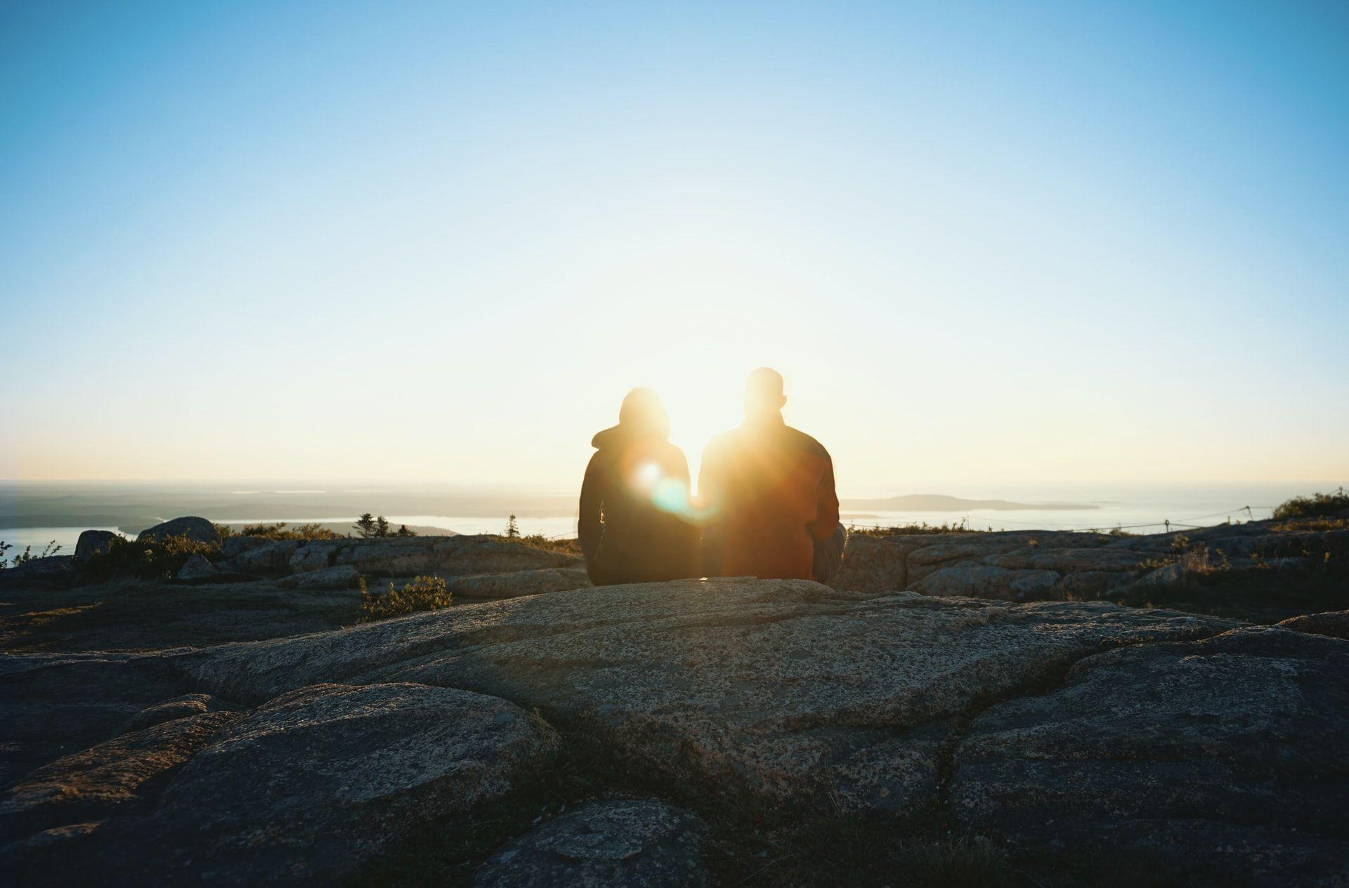 Pariskunnan siluetit kalliolla, aurinko paistaa parin takaa