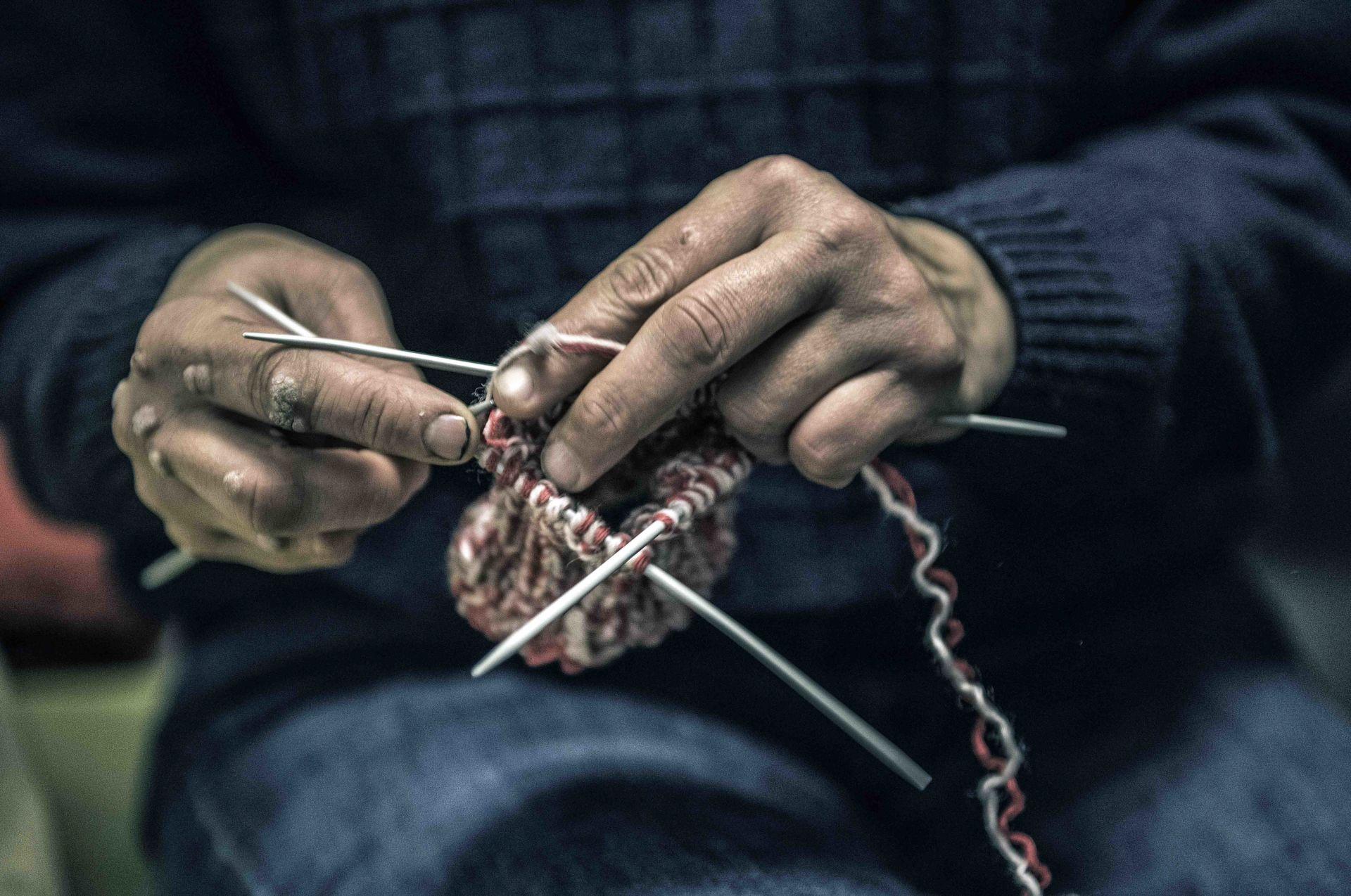 Vanha nainen neuloo villasukkaa.