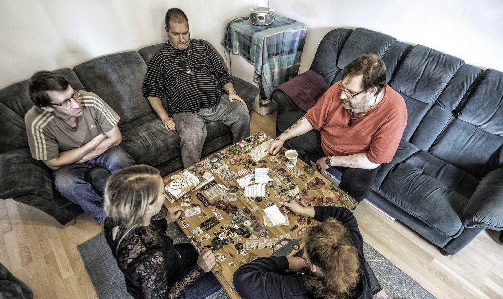 Joukko ihmisiä pelaamasaa Yatzya sohvapöydän ympärillä.