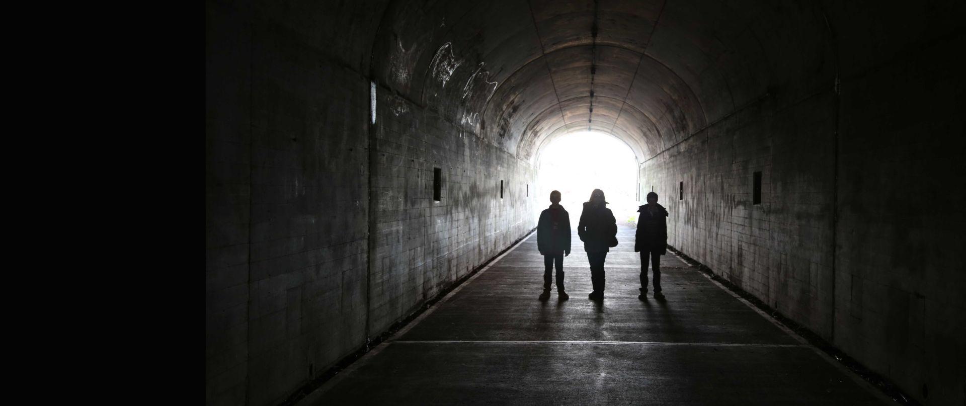 Kolme henkilöä pimeässä tunnelissa, jonka päässä näkyy valoa.