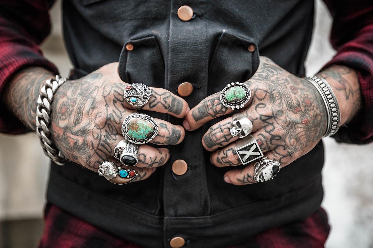 Tatuoidun käden jokaisessa sormessa sormus.