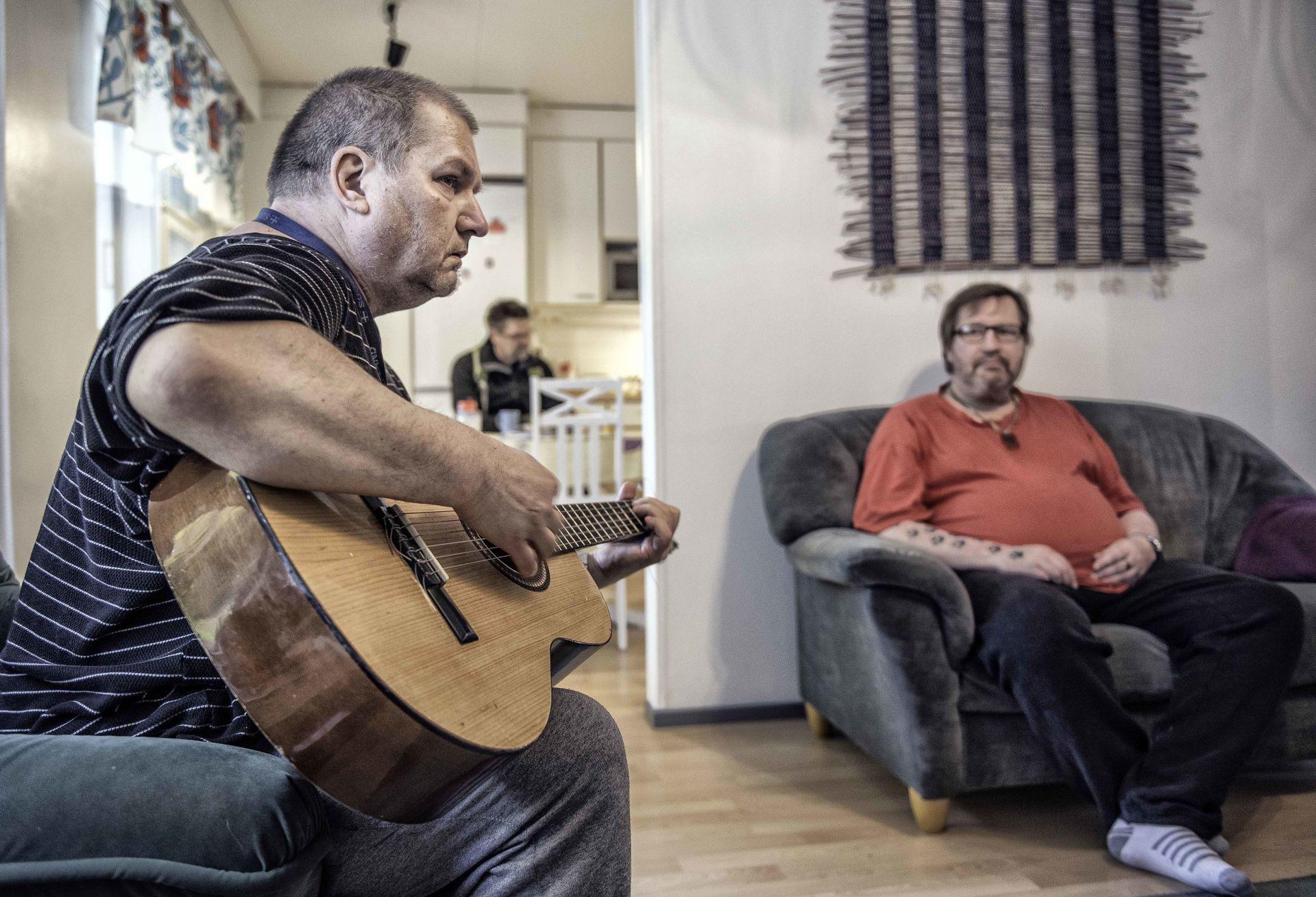 Mies soittaa kitaraa, toisen katsoessa toiselta sohvalta.