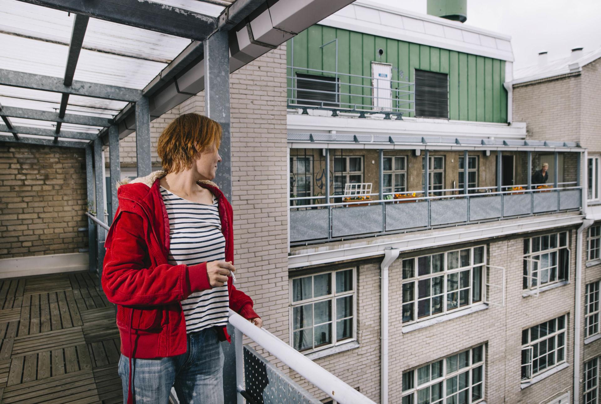 Nainen katsoo parvekkeelta kerrostalon sisäpihalle.