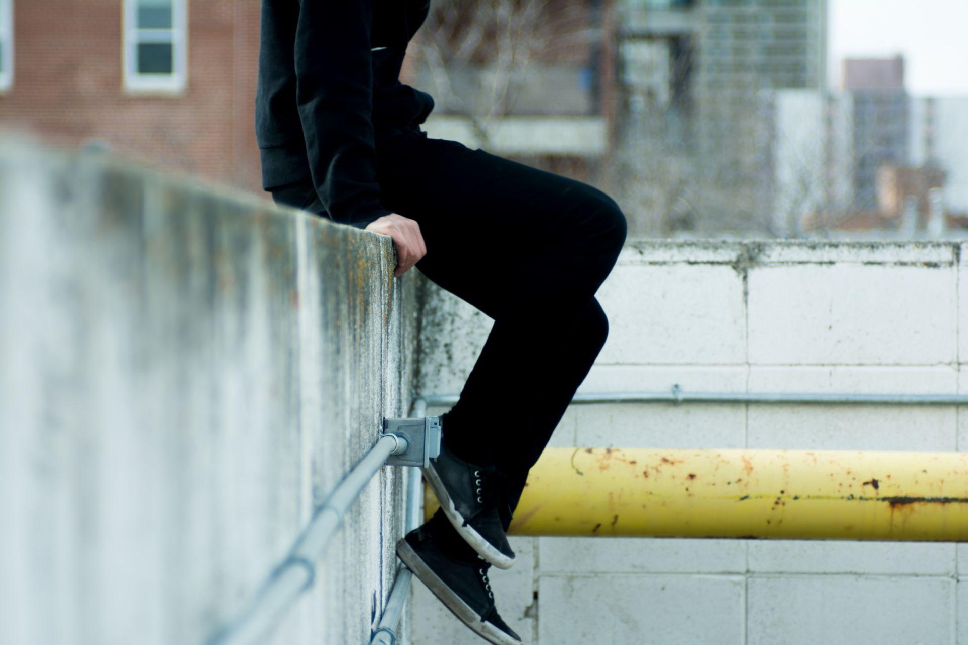 Mustiin pukeutunut nuori istuu vallin reunalla.