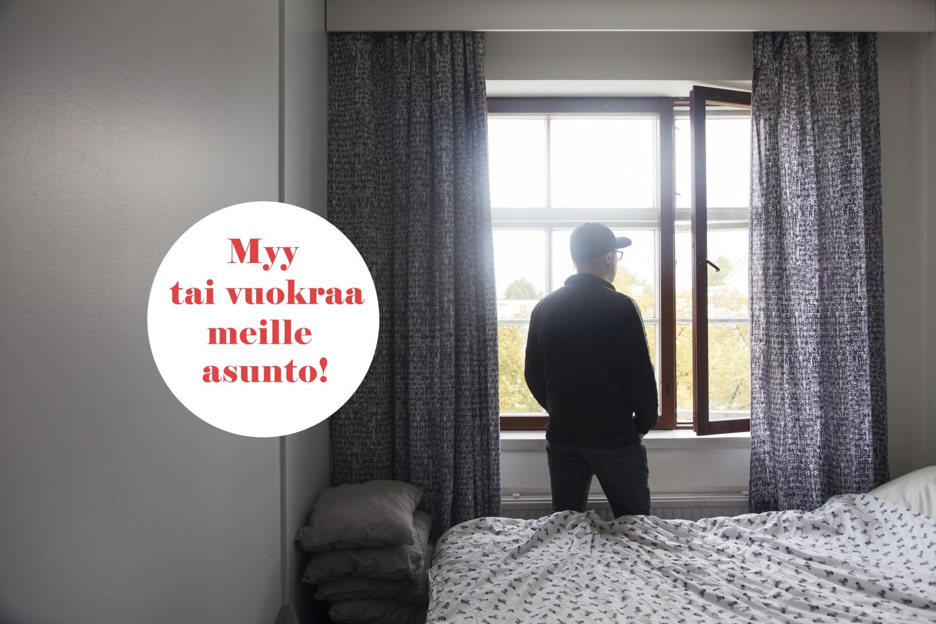 Mies katsoo makuuhuoneen ikkunasta ulos.