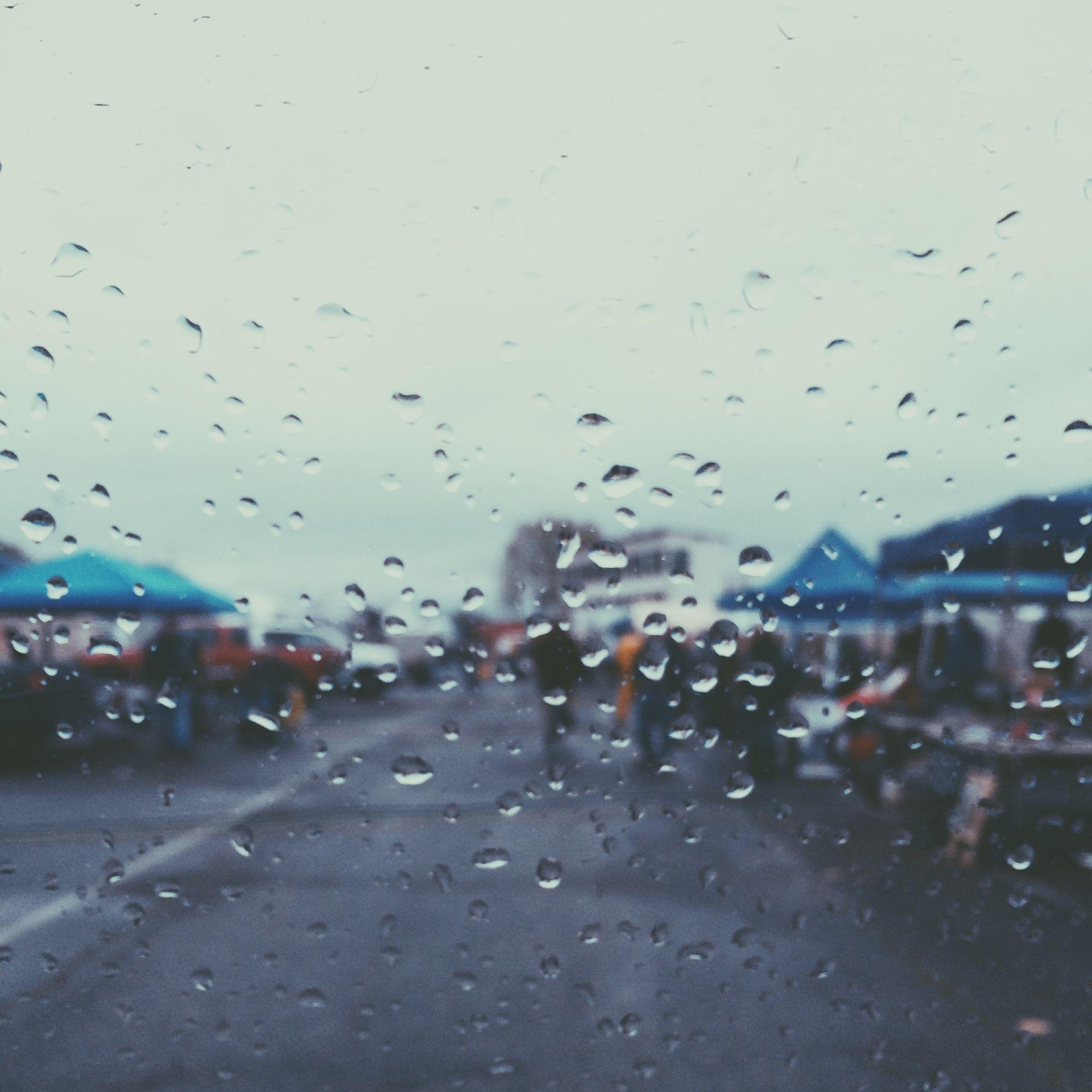 Sadepisaroita täynnä olevan lasin läpi otettu valokuva sateisesta torista.