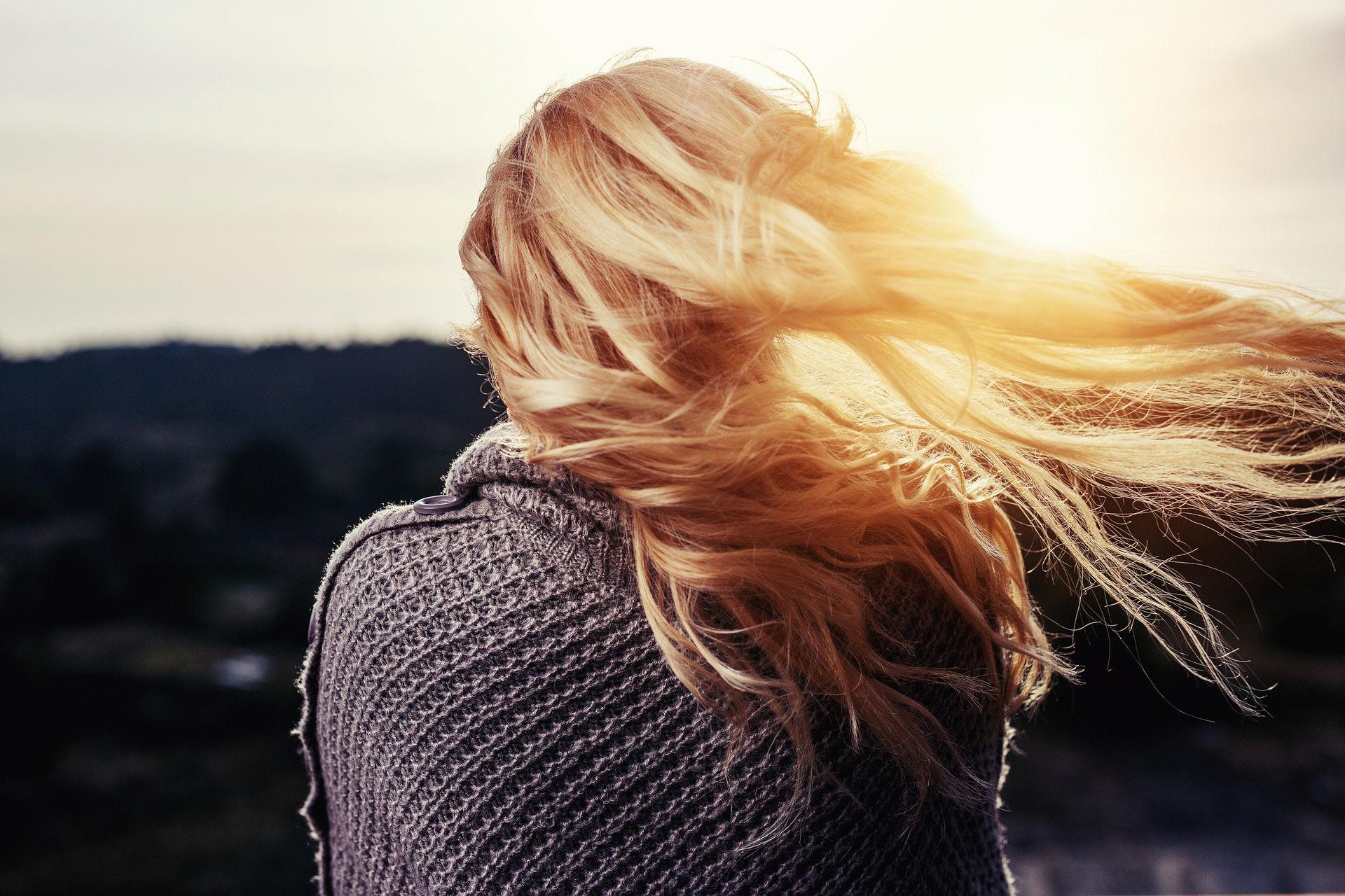 Naisen vaaleat hiukset hulmuavat tuulessa.