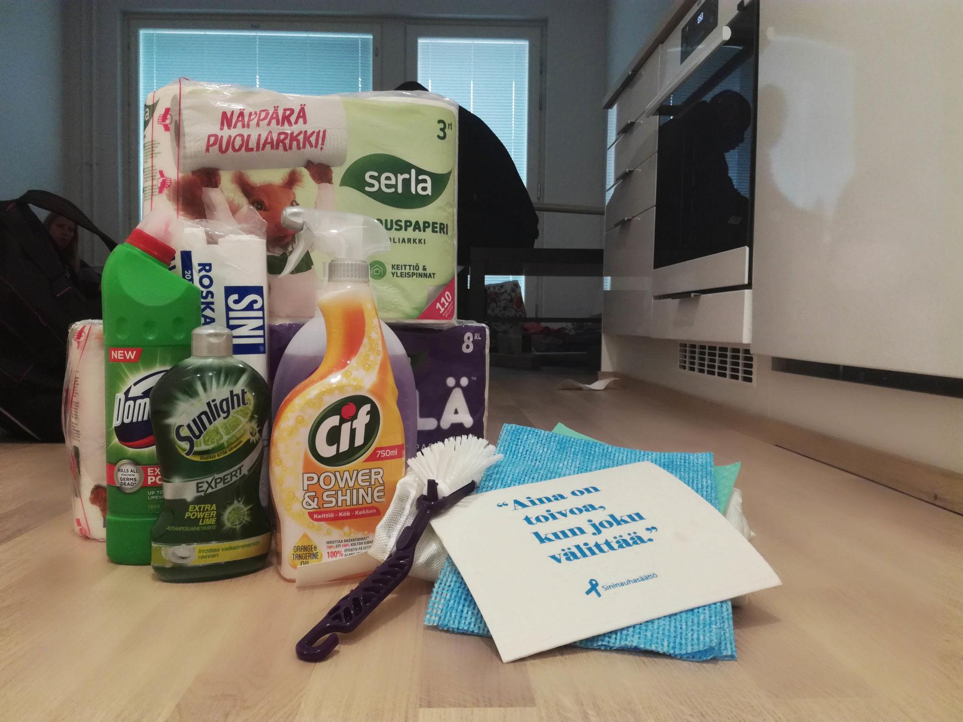 Kasa kodin puhdistusaineita, siivoustarvikkeita sekä WC- ja talouspapereita keittiön lattialla.
