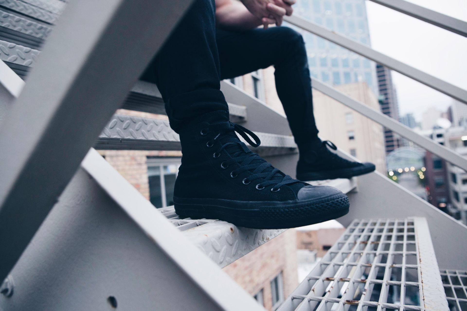 Mustiin pukeutunut henkilö istuu metalliportailla.