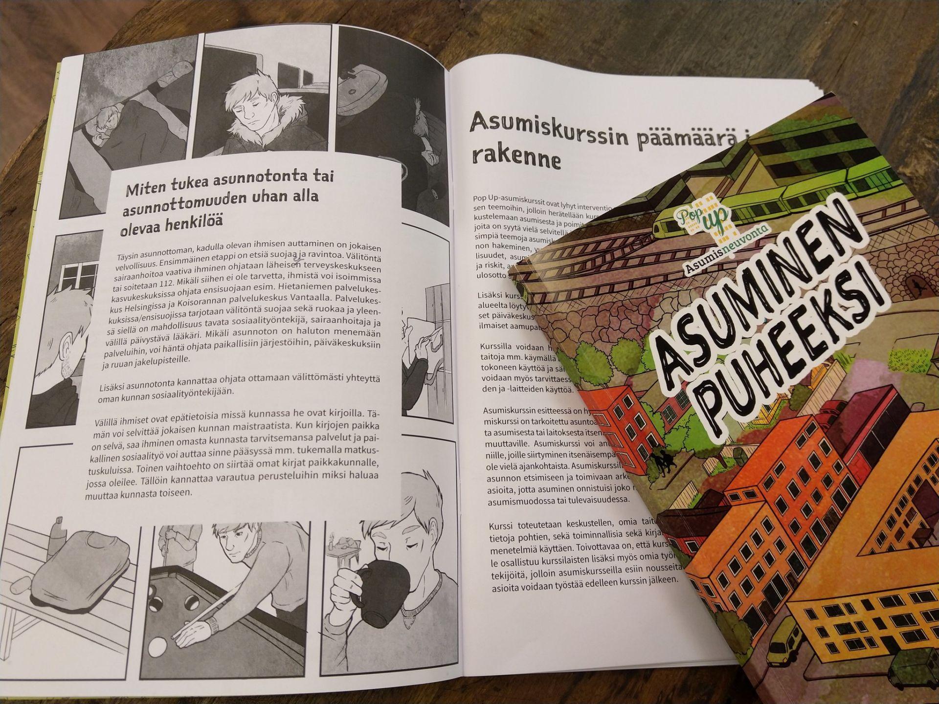 Asuminen puheeksi -opas avattuna pöydälle ja Asuminen puheeksi -sarjakuvakirja aseteltuna toisen sivun päälle.