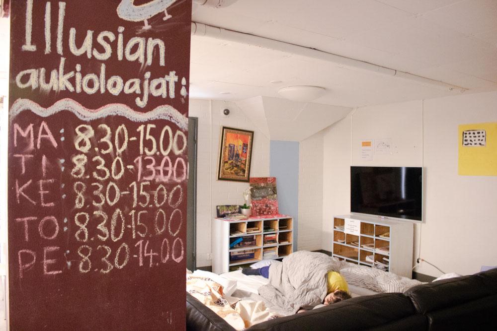 Pylväs, johon kirjoitettu Illusian aukioloajat. Pylvään takaa näkyy lattalle levitettyjä patjoja.