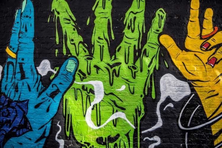 Graffiti sinisestä, vihreästä ja oranssista kädestä.