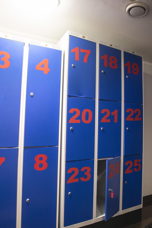 Sinisiä pukuhuonelokerikoit, joihin kirjoitettu isona numerot 1-25.