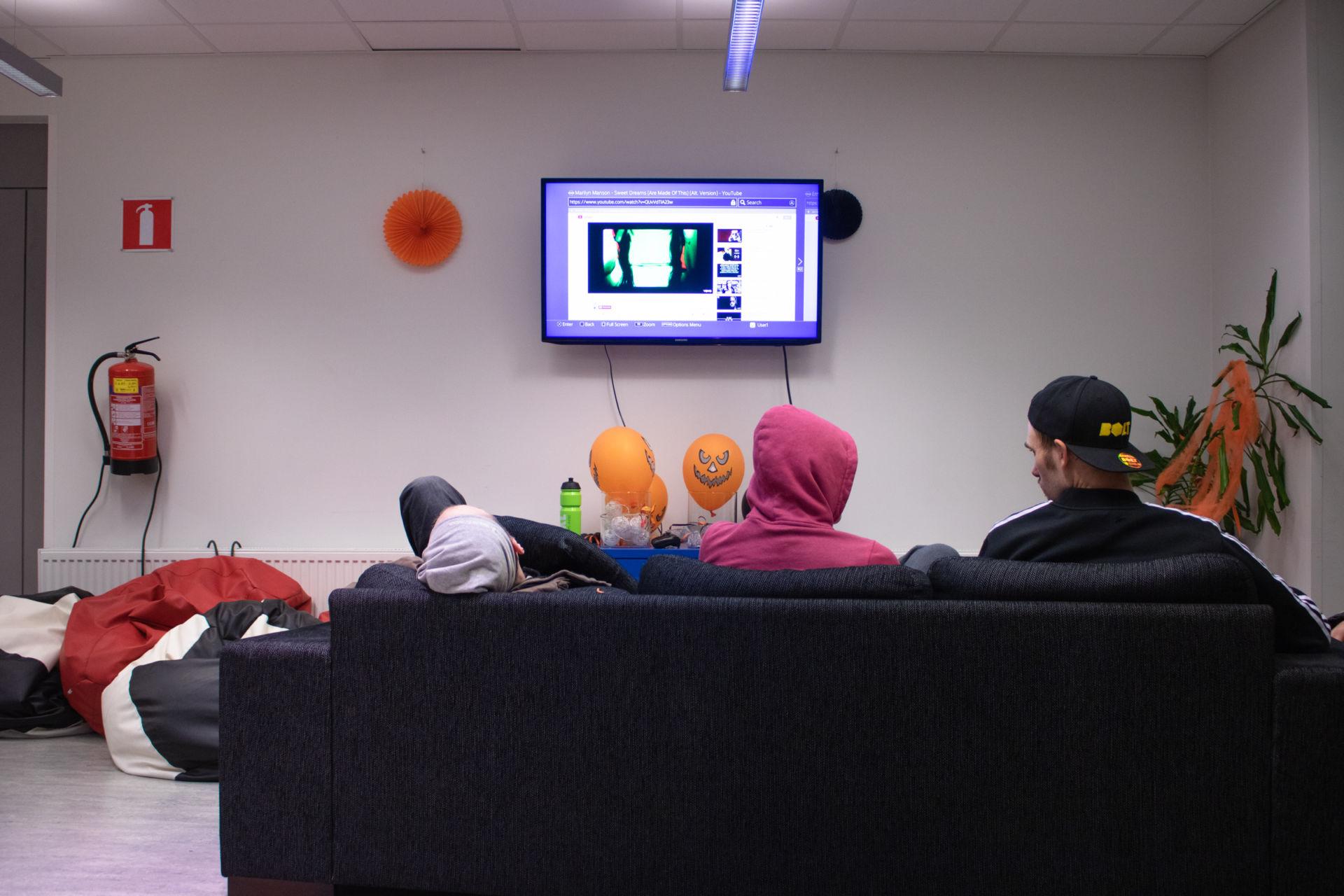 Kolme henkilöä sohvalla katsomassa Youtubea TV:stä.
