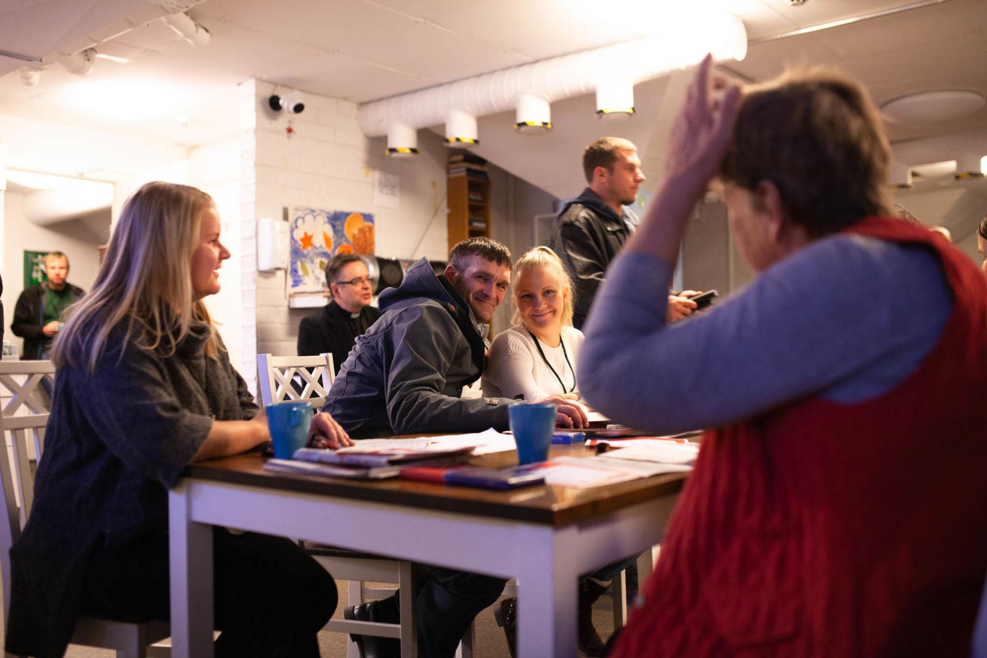 Hymyileviä ihmisiä pöydän ääressä edessään joululaulujen sanoja.