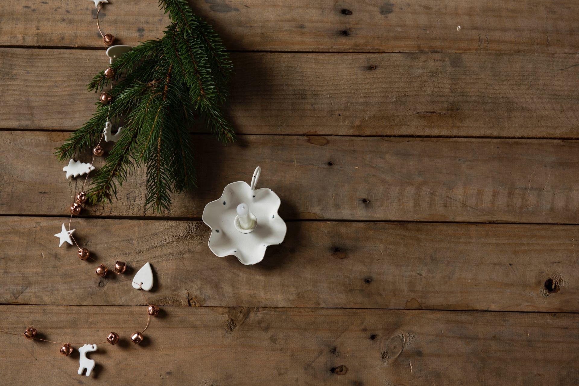 Joulukoristeita, havunoksa ja kynttilä puisella pöydällä.