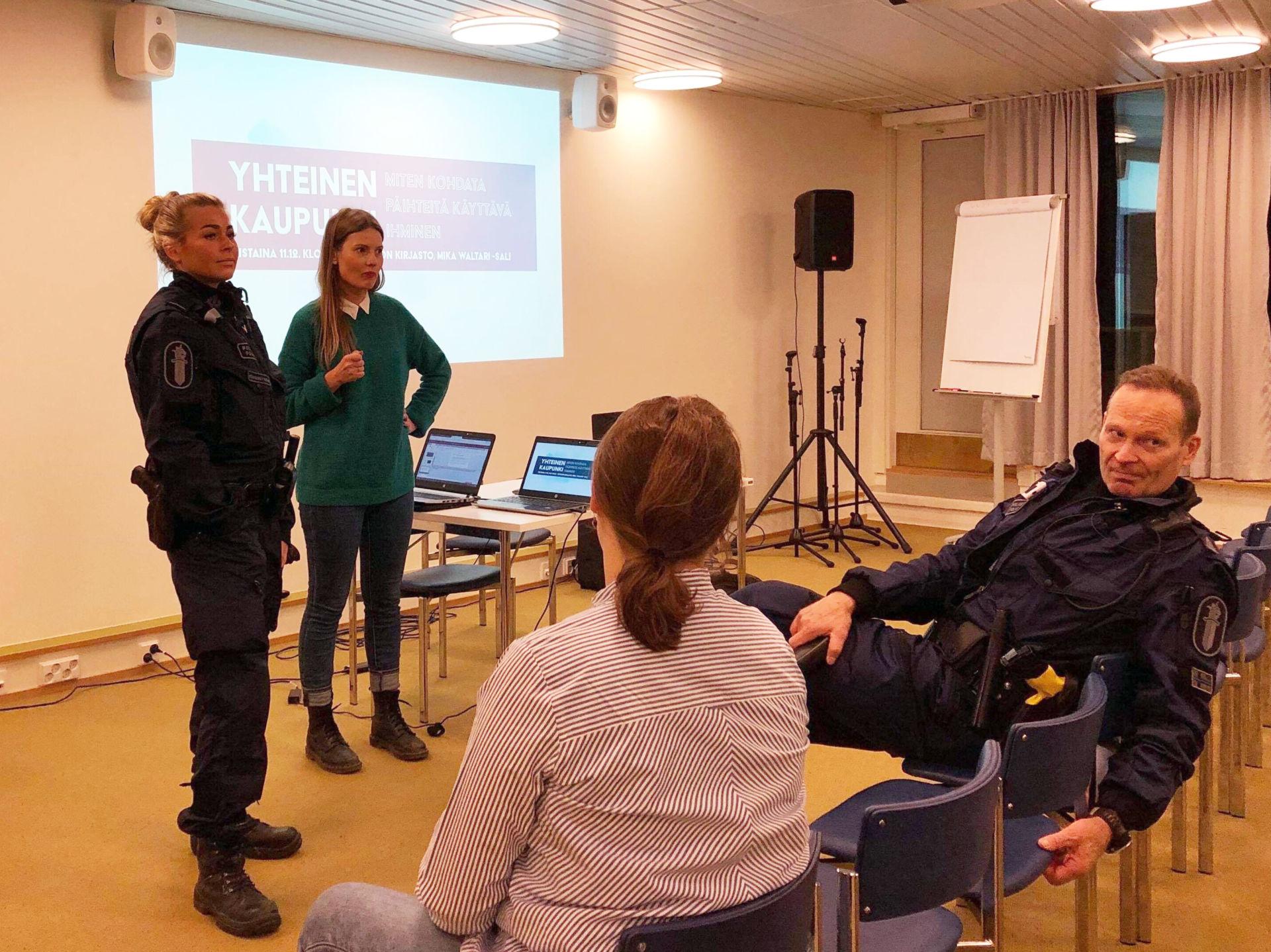 Naispoliisi ja toinen nainen pitävät luentoa. Yleisön eturivissä nainen ja mies poliisi.