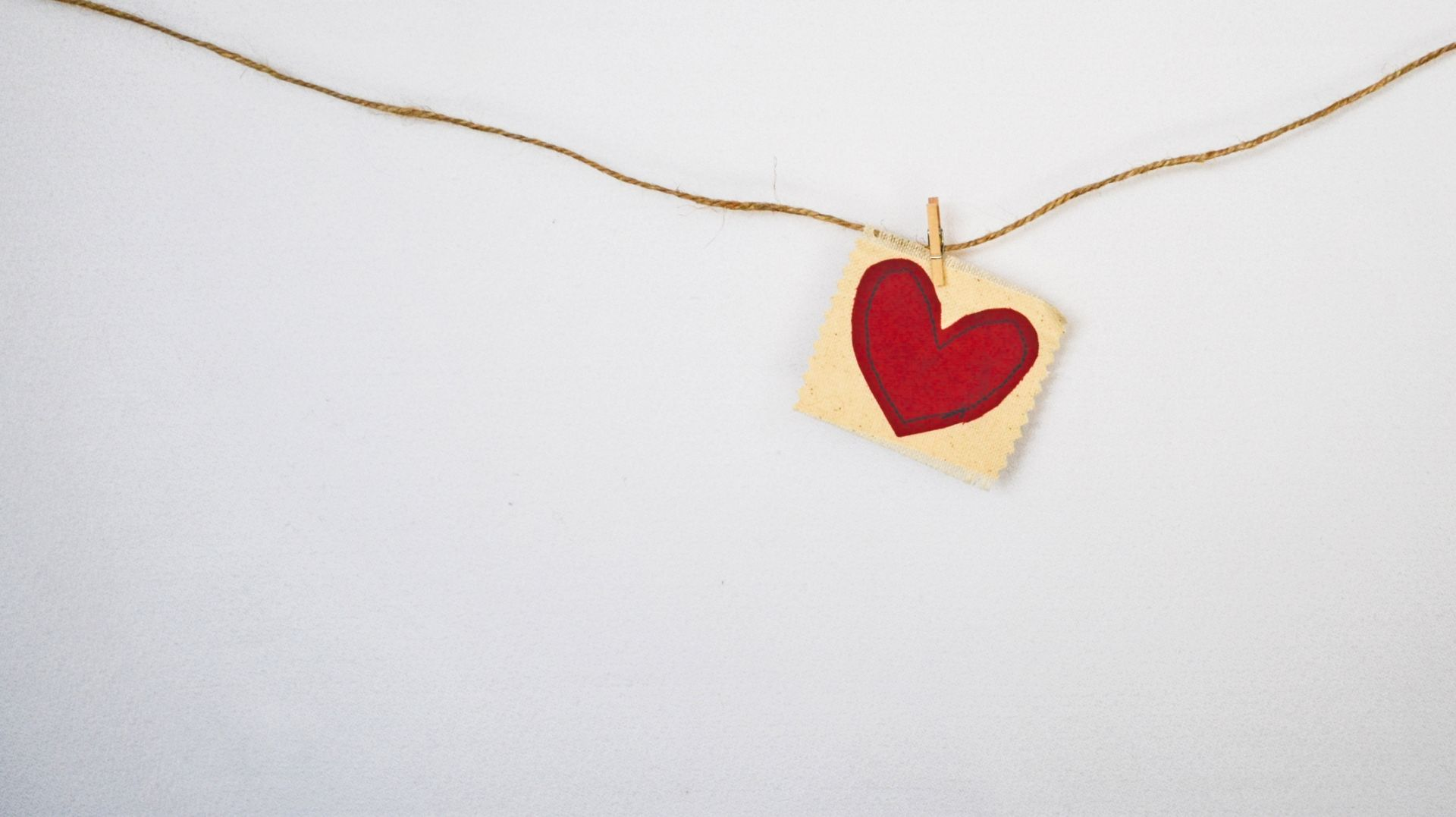 Pyykkinarulle ripustettu kankaan pala, johon on piirretty punainen sydän.