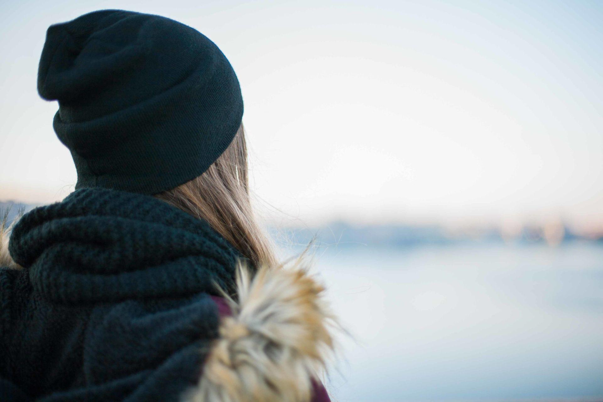 Mustapipoinen tyttö selin kameraan katsoo sumeaa lumista maisemaa.