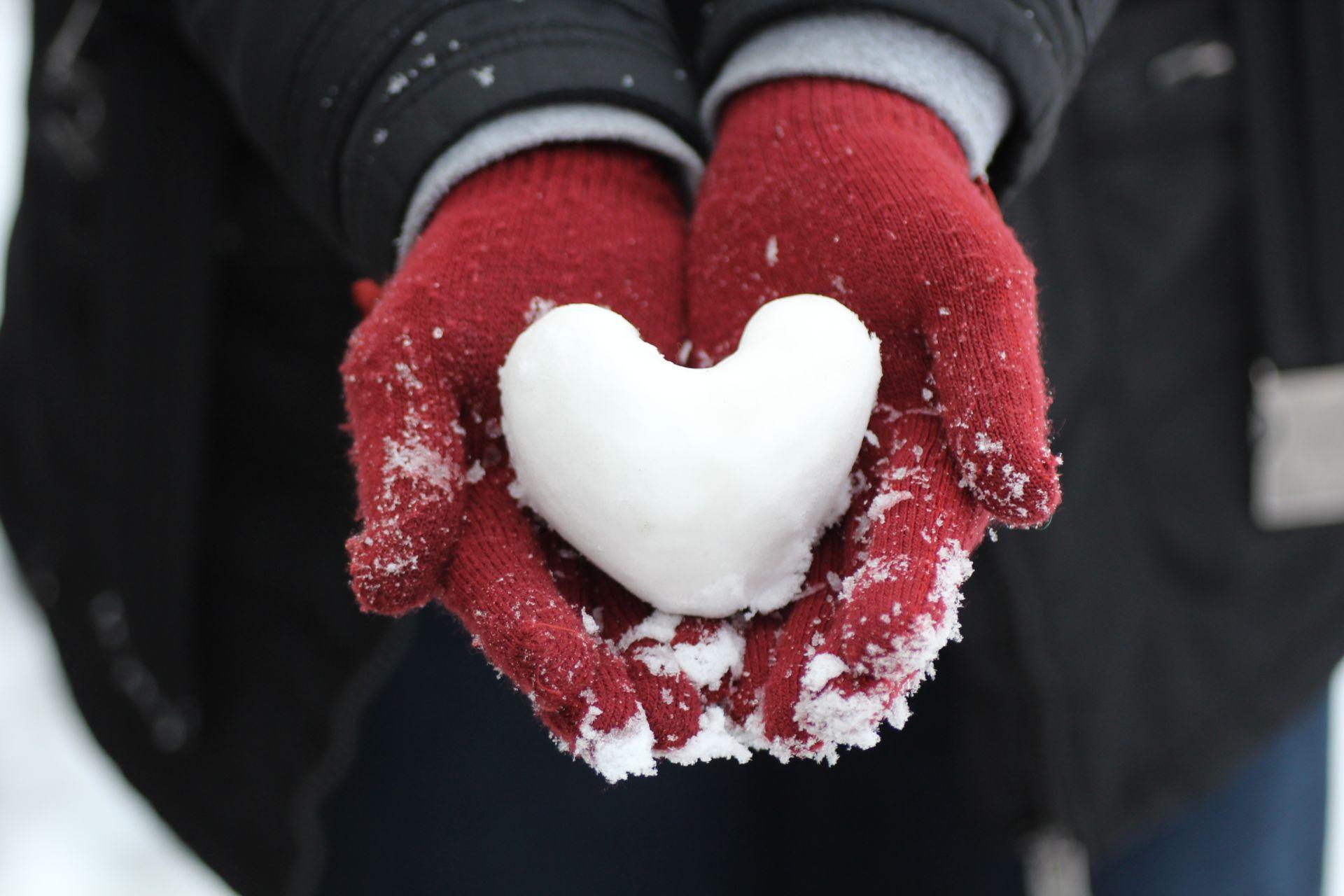 Punatumppuiset kädet pitelevät lumesta tehtyä sydäntä.