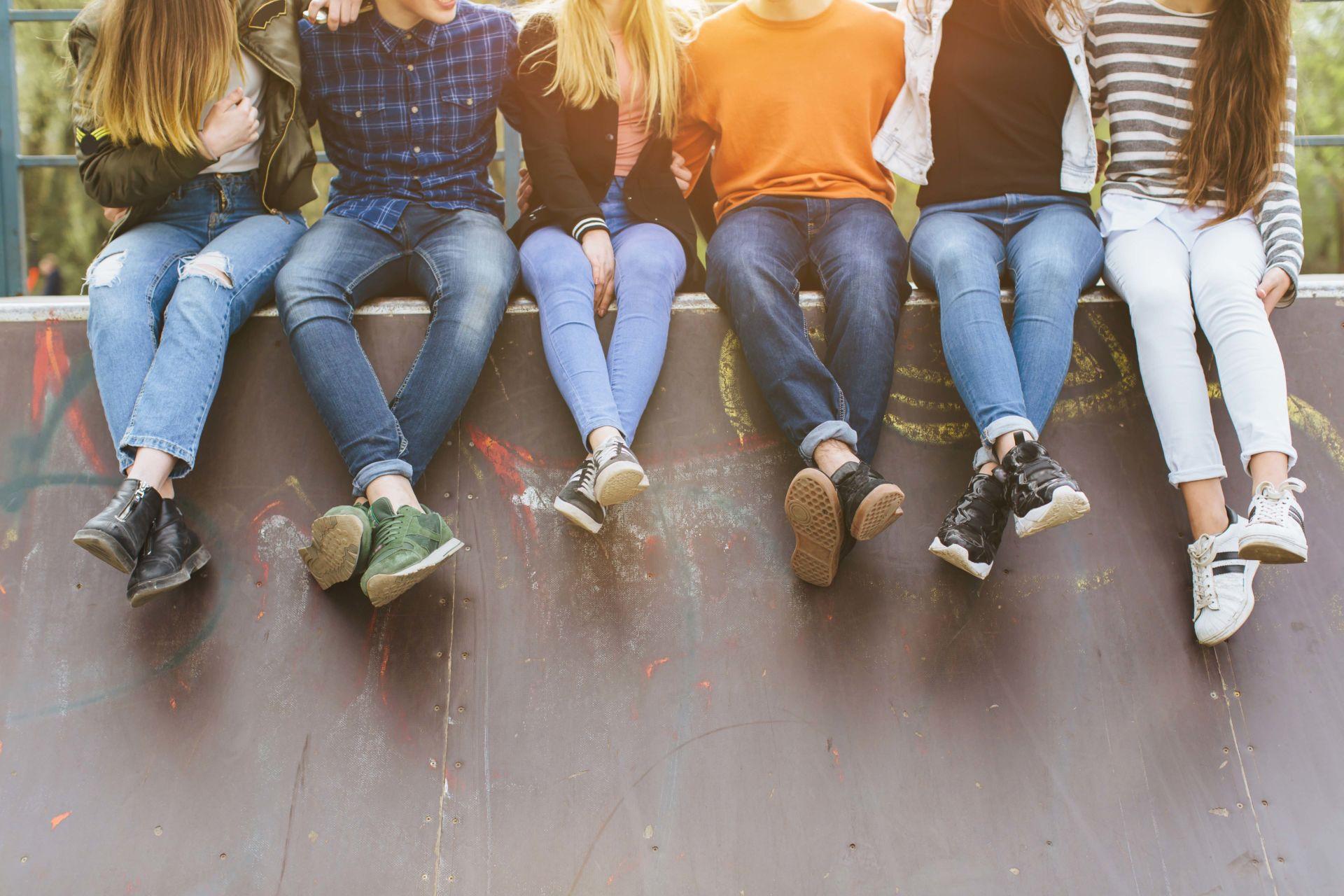 Hartioista alaspäin rajattu kuva, jossa kuusi teiniä istuu betonivallin päällä.