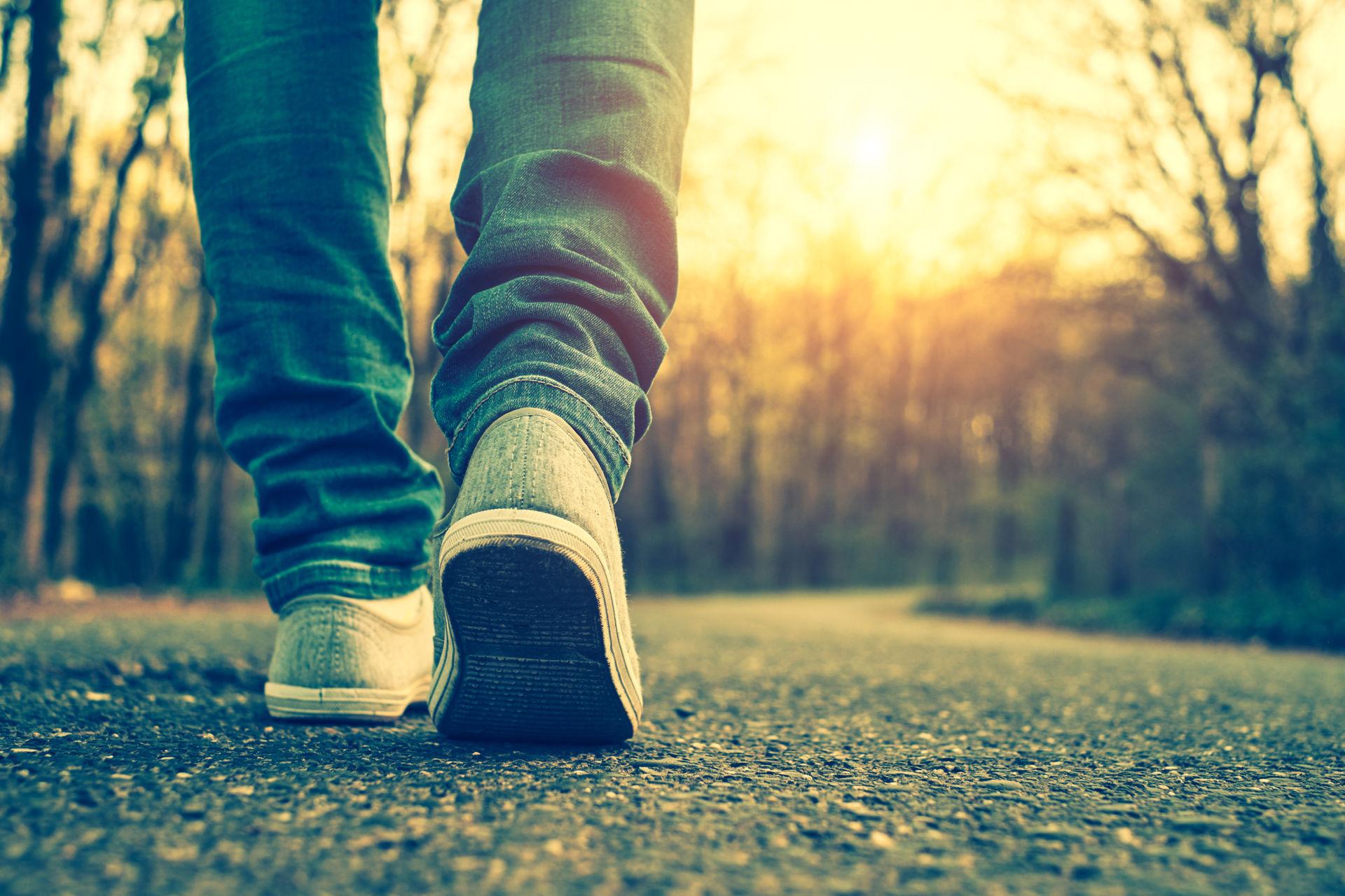 Maantasolta kuvattu kävelijä, jonka yllä on farkut ja tennarit.