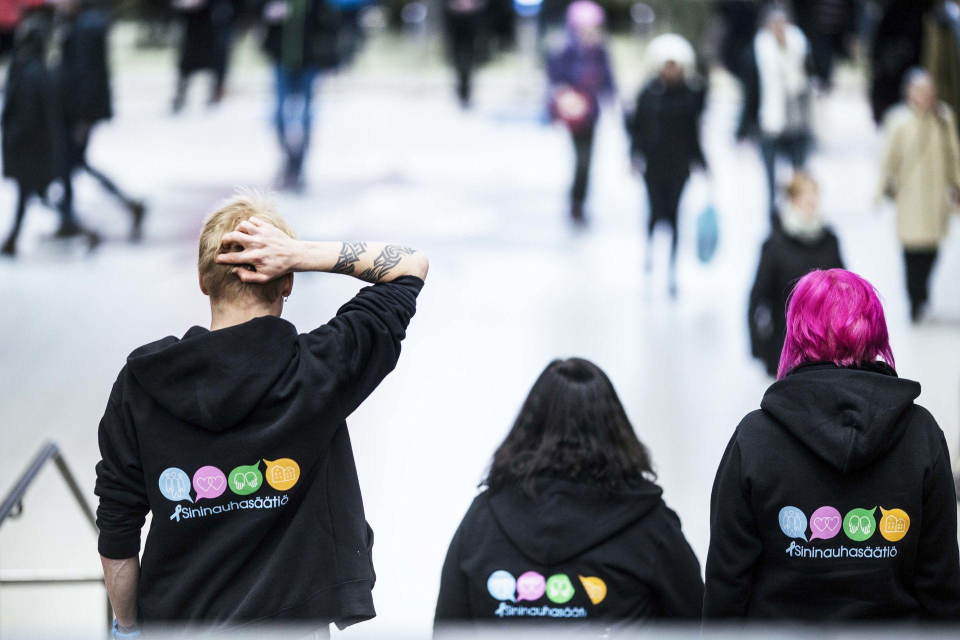 Kolme Sininauhasäätiön huppareihin pukeutunutta henkilöä seisoo selin kameraan ja katsoo kadulla kulkevia ihmisiä.