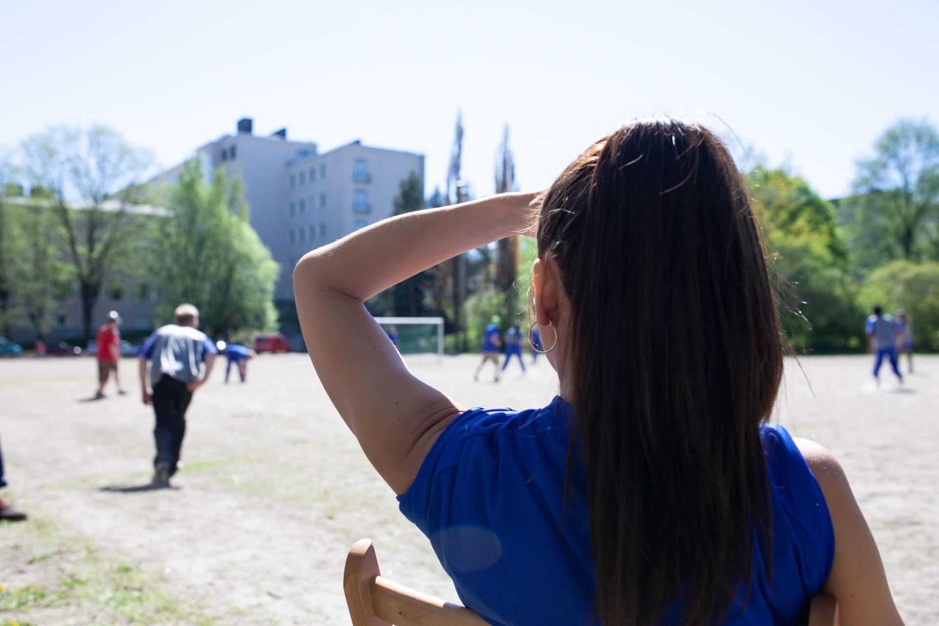 Nainen varjostaa kasvojaan kädellään seuratessaan jalkapallo-ottelua.