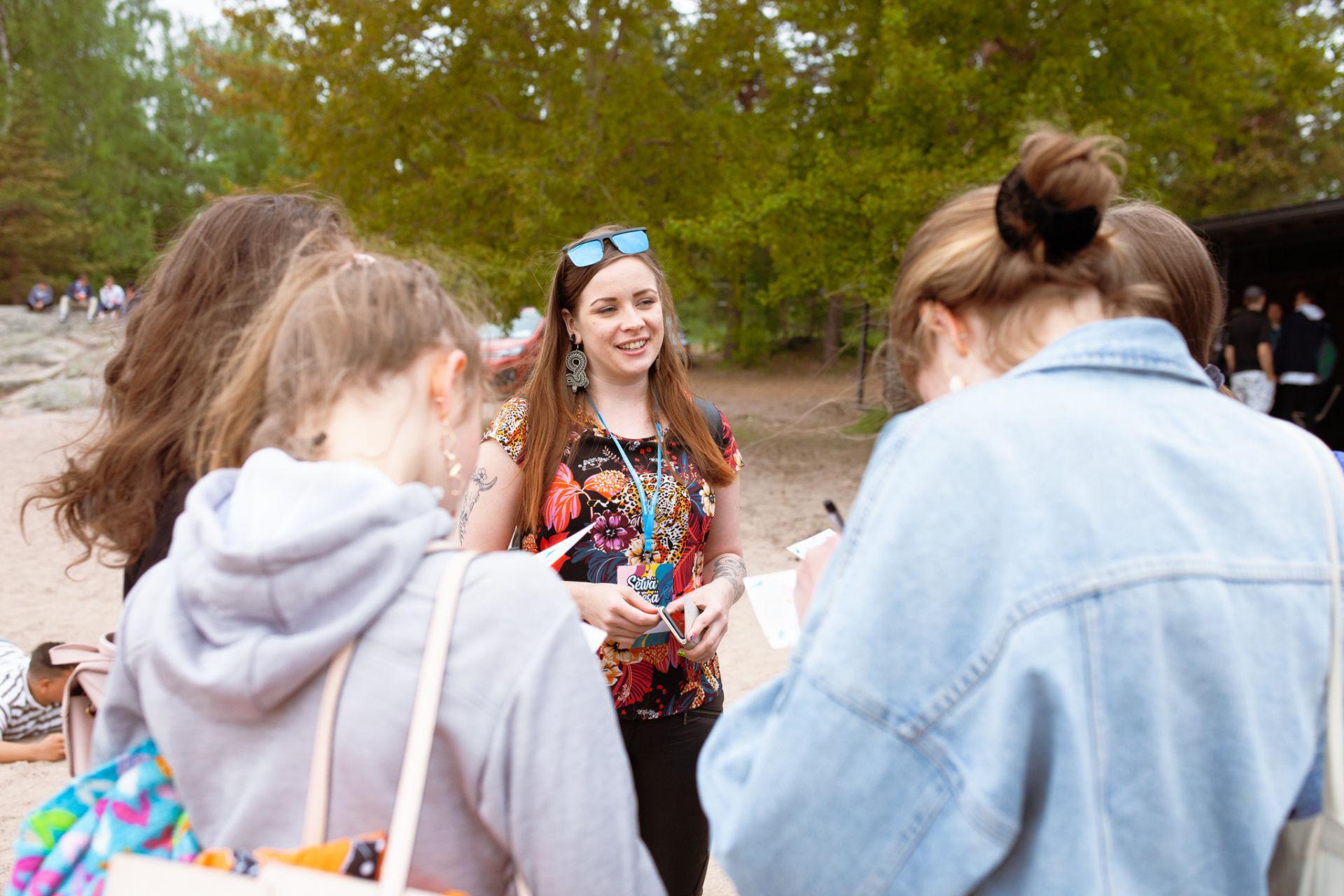Työntekijä puhuu nuorten kanssa.